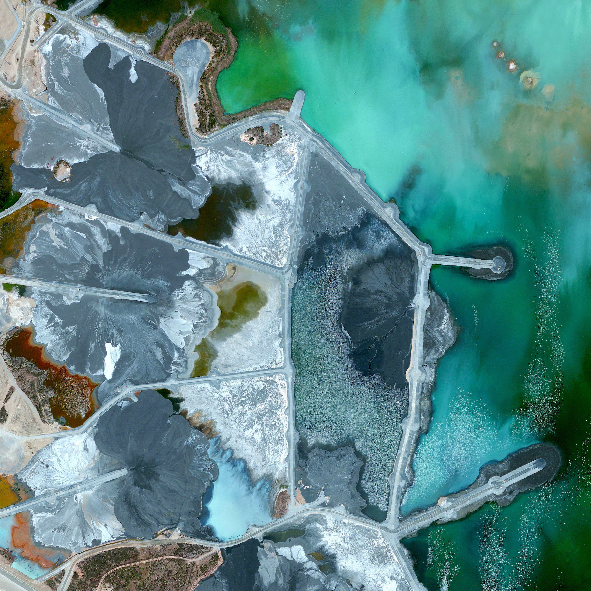 6/3/2016   Neves-Corvo Mine   Castro Verde Municipality, Portugal  37°34′23″N 7°58′15″W    Waste ponds are seen at the Neves-Corvo Mine in the Castro Verde Municipality in Portugal. Zinc and copper and the primary resources extracted from the mine and the byproducts of that extraction is sent to these basins three kilometers away. Typically, once waste materials are pumped into a tailings pond, they are mixed with water to create a sloppy form of mud known as slurry. The slurry is then pumped through magnetic separation chambers to extract usable ore and increase the mine's total output.