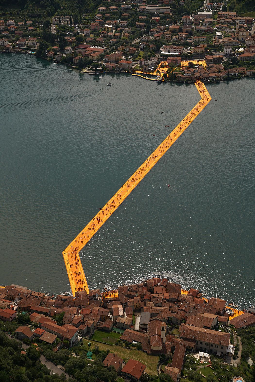 """The Floating Piers"" is a temporary, public art installation by artists Christo and Jeanne-Claude that is currently on display on top of Lake Iseo in Lombardy, Italy. Its vibrant, yellow walkways are constructed with 70,000 square meters of fabric, carried by a modular floating dock system of 200,000 high-density polyethylene cubes. Floating Piers will remain open to public until July 3rd this summer.  Photo by @wolfgangvolz"