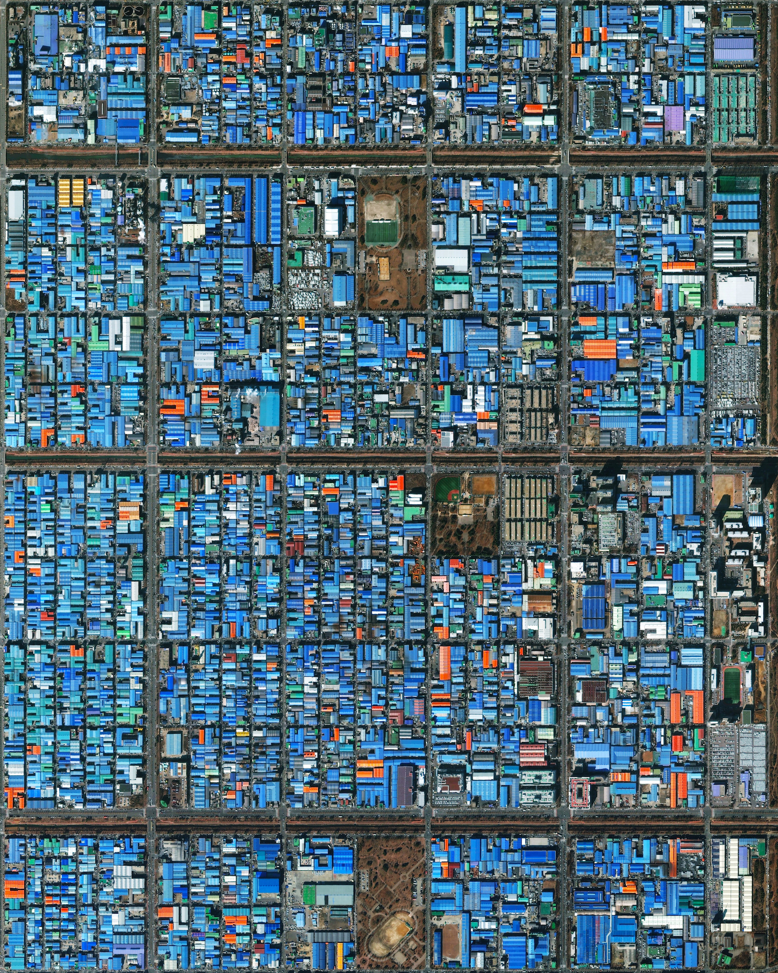 7/2/2016  Jeongwang-dong  Ansan, South Korea  37.336147372°, 126.718586767°     Jeongwang-dong is an industrial sector in the city of Ansan, South Korea. The Korean government intensively drove a plan to develop the modern city, particularly in this area, with an emphasis on manufacturing. The striking blue color that you see here results from the use of aluminum roofing, which is used for its low cost and longevity.