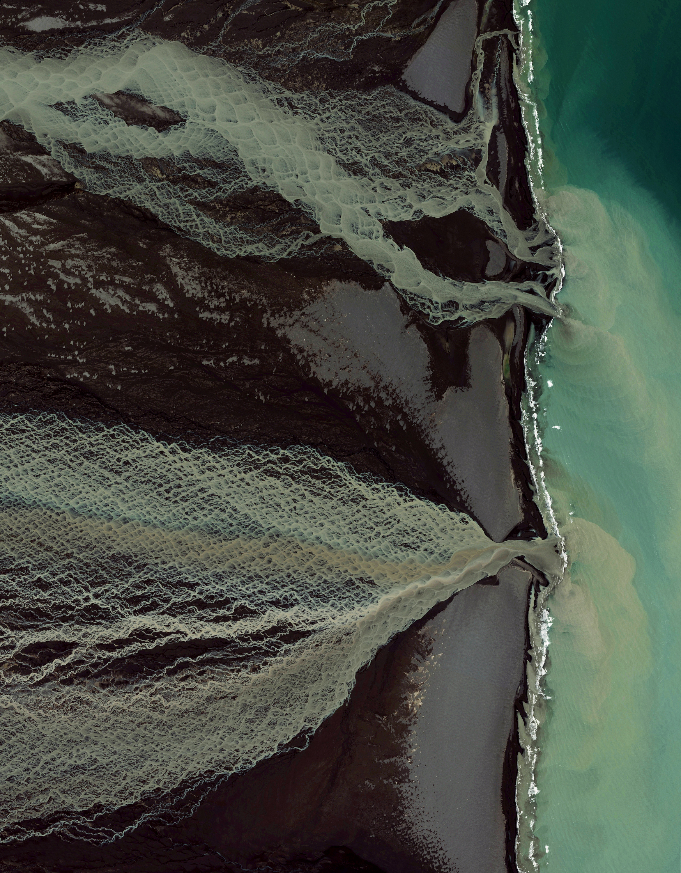 9/8/2016  Glacial melt  Skafta River, Iceland  63.7751116, -18.09628    Glacial melting and flooding occurs every year by the Skafta River in Iceland. As the water travels down towards the North Atlantic Ocean, incredible patterns are created on the hillsides. Rising lava, steam vents, or newly opened hot springs can all cause this rapid ice melt, leading to a sizable release of water that picks up sediment as it flows down from the glaciers.