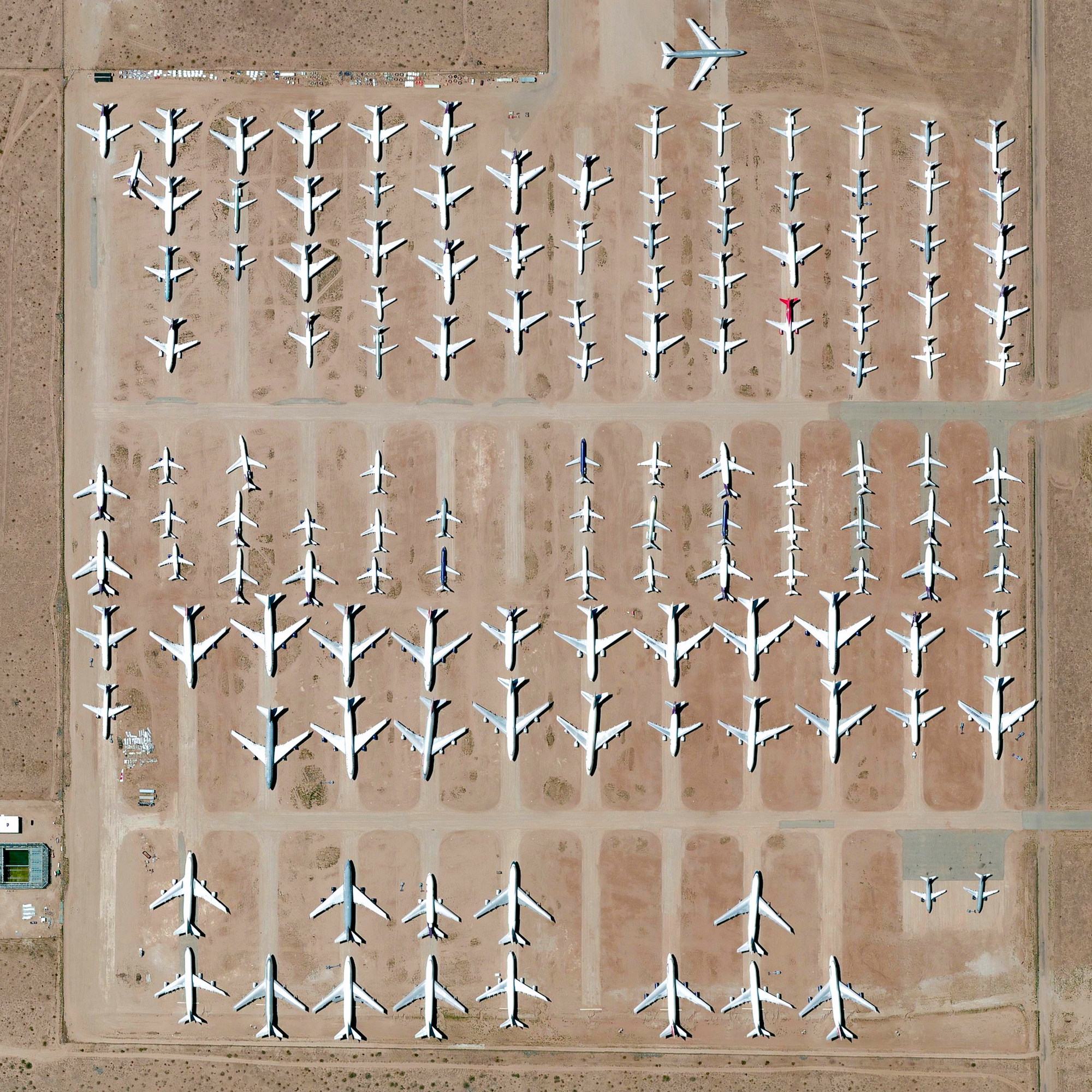 """10/19/2016  Southern California Logistics Airport  Victorville, California, USA  34°35′51″N 117°22′59″W    Here's one of my favorite images from the Where We Waste chapter of """"Overview"""". The Southern California Logistics Airport in Victorville, California contains an aircraft boneyard with more than 150 retired planes. Because the demand for jumbo jets has dropped significantly in the last two decades in favor of smaller, more affordable twin‑engine planes, many large aircrafts such as Boeing 747s have been retired. The dry conditions in Victorville – located on the edge of the Mojave Desert – limits the corrosion of metal, meaning planes can be stored here for years while they are stripped for spare parts."""