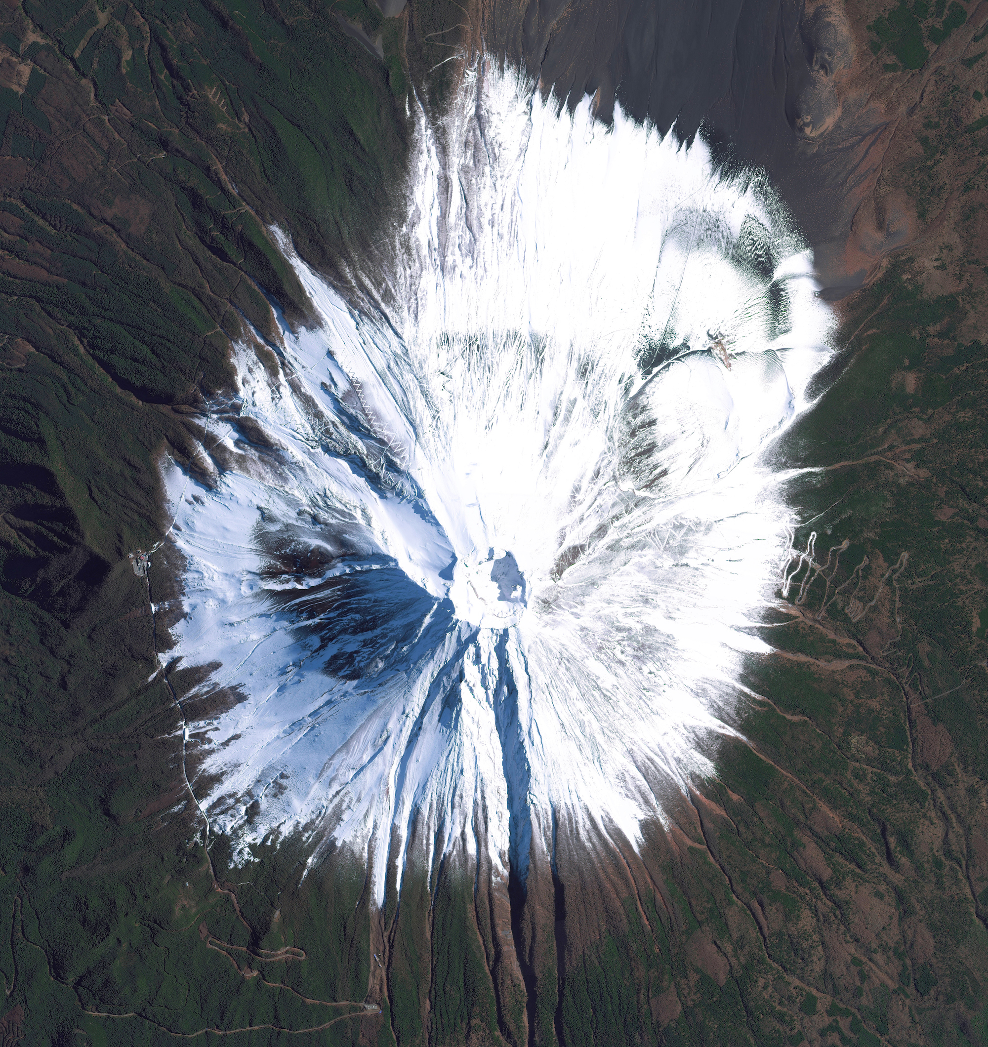 """Our new book """"Overview"""" contains 70 images that have never been posted on our feed before! Here's one that captures the natural beauty of Mount Fuji —an active stratovolcano and the tallest peak in Japan, rising 3,776 meters (12,389 feet). As seen in this Overview, Fuji has an extremely symmetrical cone, which is snow‑capped several months of the year. During warmer months, climbing routes make it possible for hundreds of thousands of people to scale the volcano each year."""