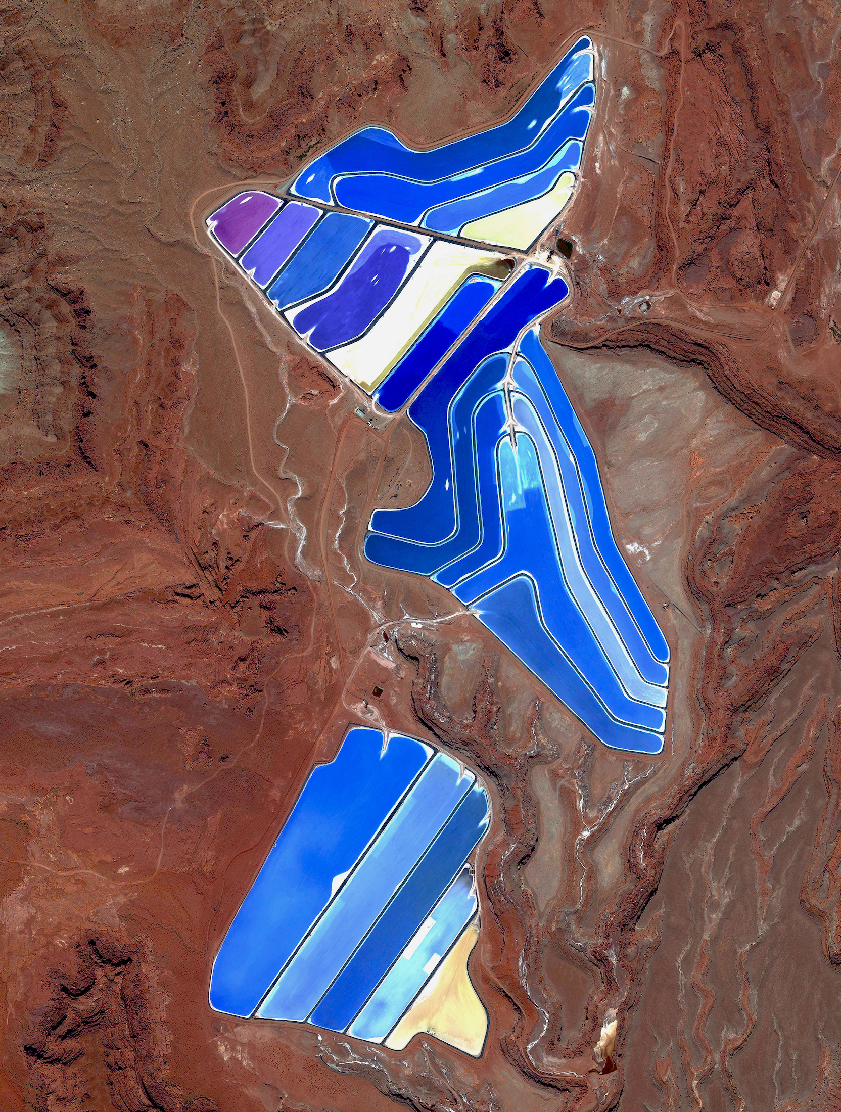 1/18/2017  Moab Evaporation Ponds  Moab, Utah, USA  38·485579°, –109·684611°    Evaporation ponds are visible at the potash mine in Moab, Utah, USA. The mine produces muriate of potash, a potassium-containing salt that is a major component in fertilizers. The salt is pumped to the surface from underground brines and dried in massive solar ponds that vibrantly extend across the landscape. As the water evaporates over the course of 300 days, the salts crystallize out. The blue color seen here occurs because the water is dyed a deep blue, as darker water absorbs more sunlight and heat, thereby reducing the amount of time it takes for the water to evaporate and the potash to crystallize.  This image was also just featured in a fantastic interview by Perrie Hartz at Indigare Magazine. You can check it out  here .