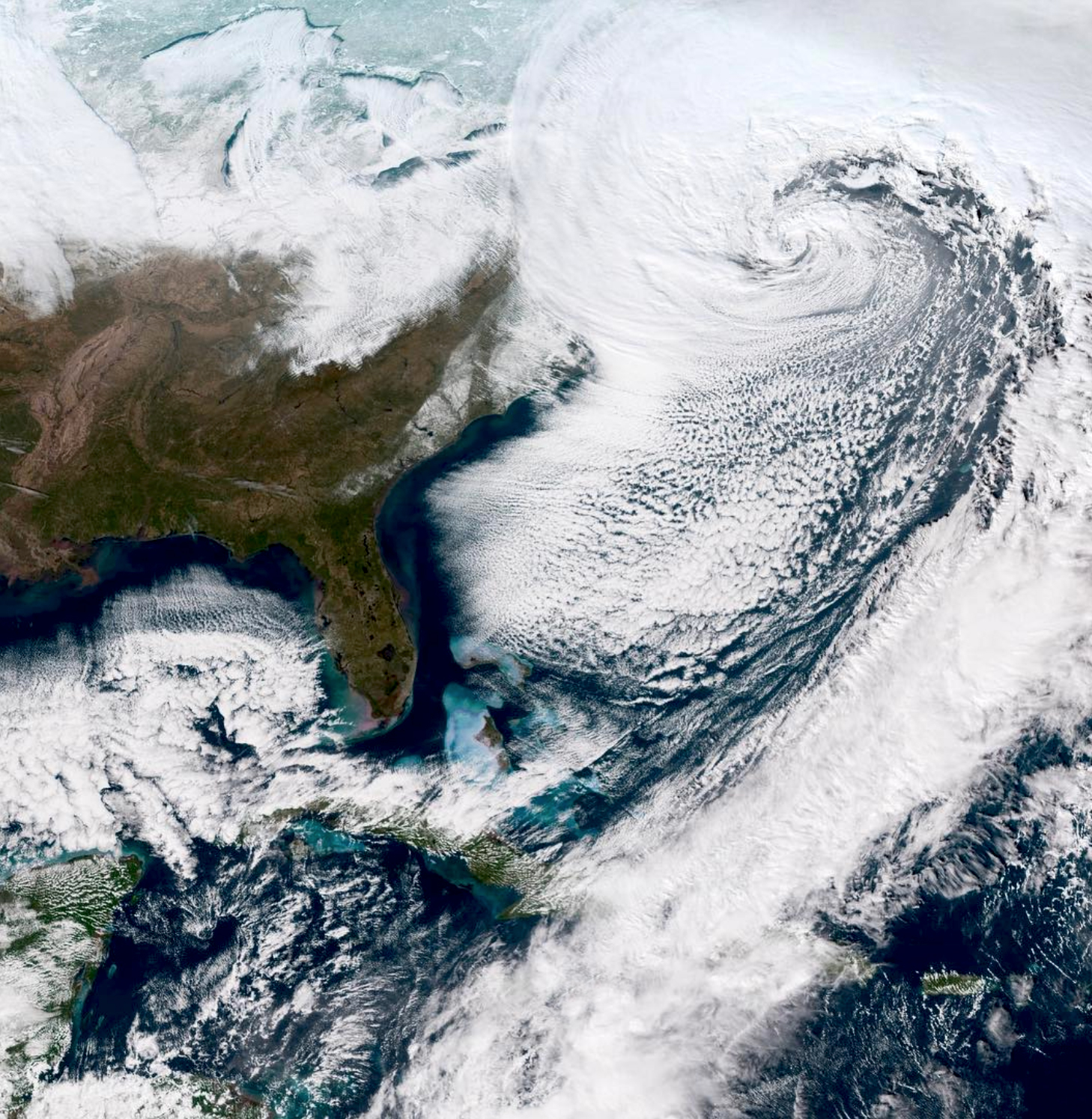 """Check out this incredible view of the """"Bomb Cyclone"""" - the powerful winter storm currently making its way toward the northeastern United States. From this vantage point in outer space, we can see the center of the low pressure area and a thick band of clouds bringing even more snow and gusty winds from the Mid-Atlantic states towards New England. The term """"bomb cyclone"""" refers to the intensification of the storm that happens when an extreme drop of pressure occurs in a short period of time."""