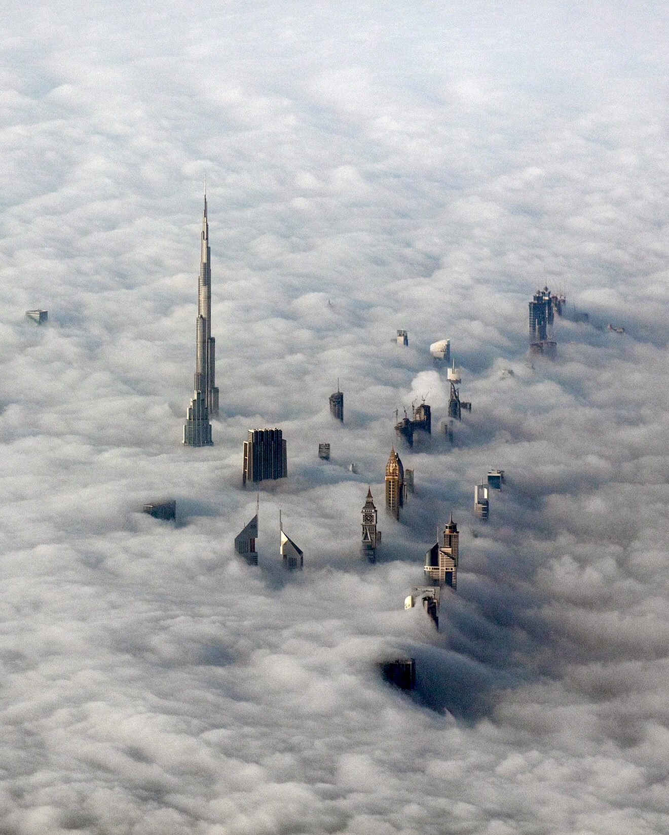 Check out this photograph of skyscrapers peeking through the clouds over Dubai. The city, located in the United Arab Emirates, has built more skyscrapers higher than 2/3 km, 1/3 km, or ¼ km than any other city on the planet. The Burj Khalifa, the world's tallest building at 829.8 meters (2,722 feet), is visible at left in this shot.  Photograph by Carsten Witte