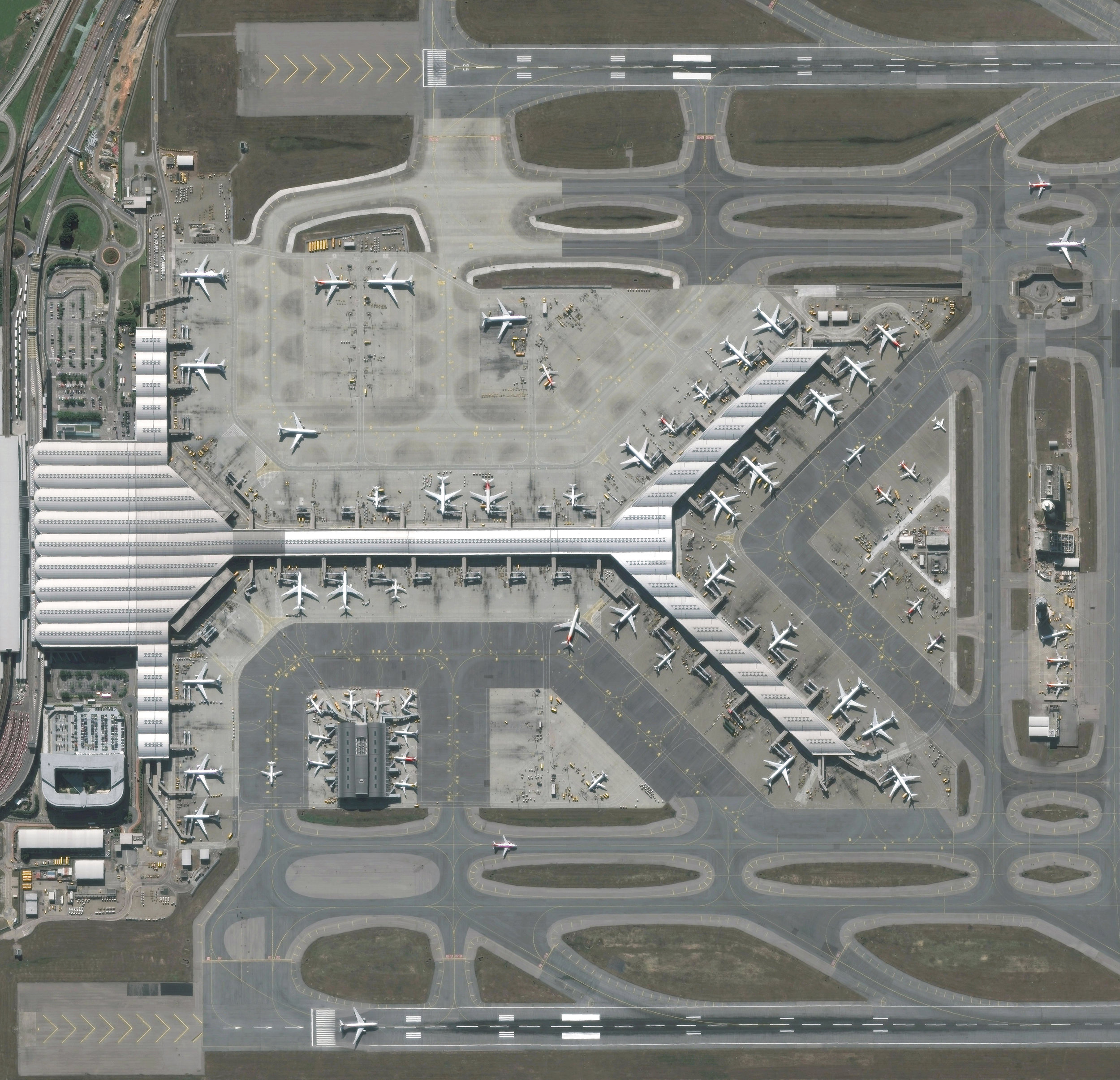 """Hong Kong International Airport is located on Chek Lap Kok, an island in Hong Kong's western waters. It is the world's busiest cargo gateway and also one of the busiest passenger airports on Earth, handling upwards of 65 million passengers a year. Terminal 1, seen here, measures 570,000 square meters (6.1 million square feet), making it the third largest passenger terminal in the world.  22°18'48.8""""N, 113°55'49.8""""E  Source imagery: DigitalGlobe"""