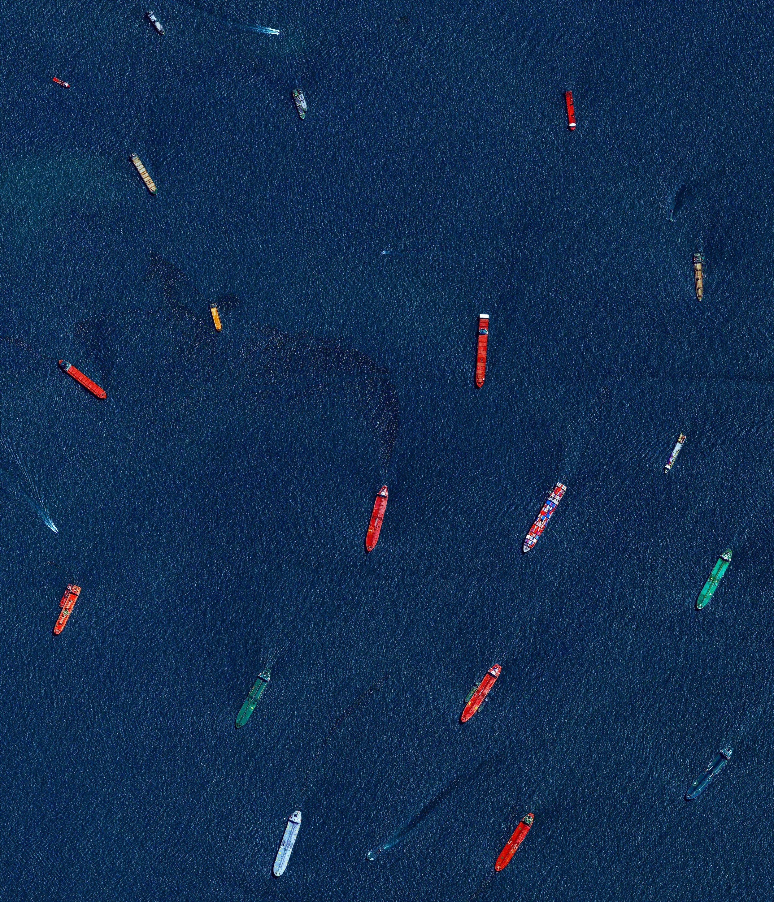"""Check out this Overview, which captures cargo ships and tankers — some weighing up to 300,000 tons — outside of the entry to the Port of Singapore. The facility is the world's second-busiest port in terms of total tonnage, shipping a fifth of the world's cargo containers and half of the world's annual supply of crude oil.  1°15'21.4""""N, 103°46'51.6""""E  Source imagery: DigitalGlobe"""