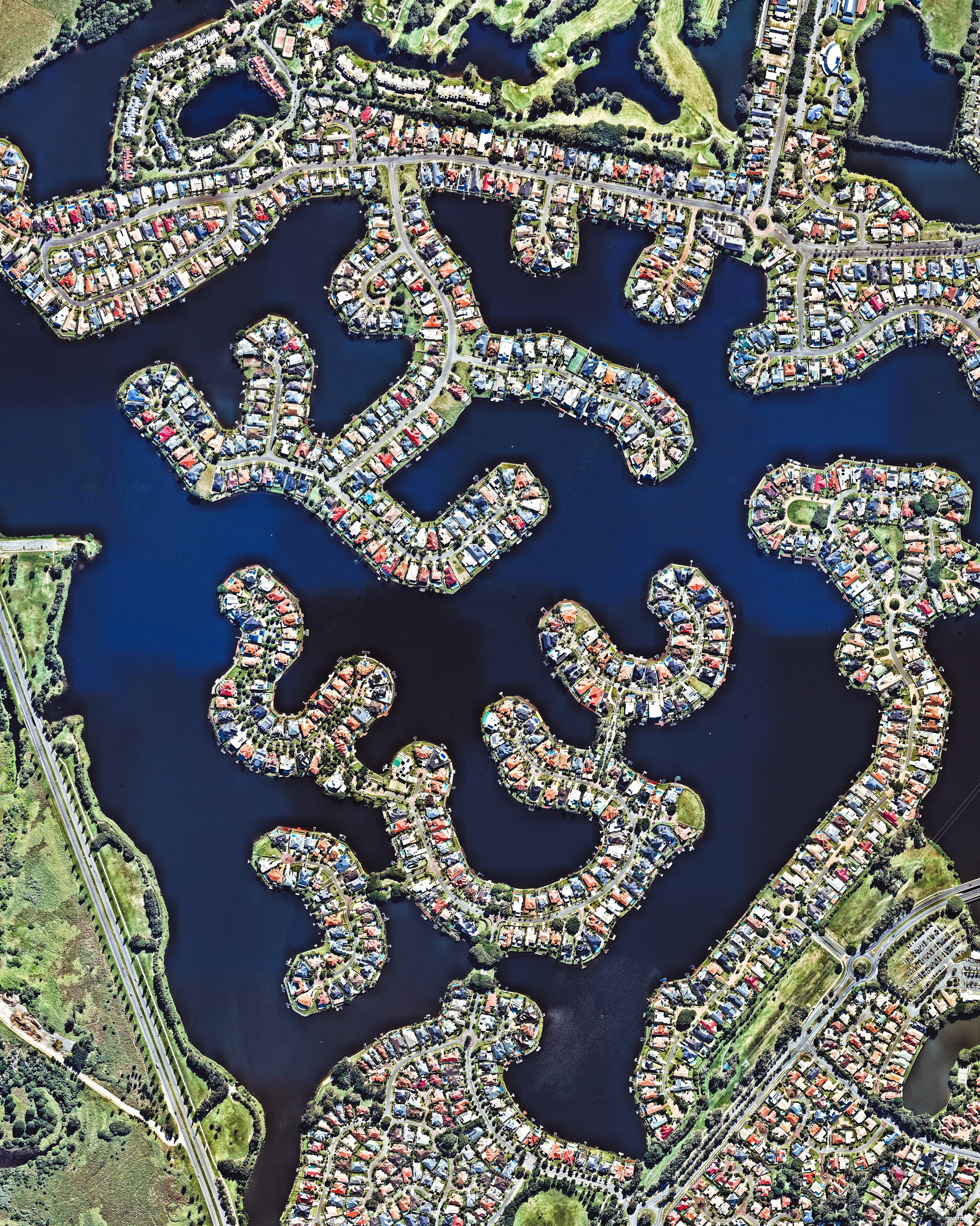 """Clear Island Waters is a suburb on the Gold Coast in Queensland, Australia. Built around artificial canals, it is a residential community that is home to roughly 4,000 people. Clear Island Waters is just a few miles west of Mermaid Beach, one of many beaches along the Gold Coast's 43-mile coastline.  28°02'40.2""""S, 153°23'51.4""""E  Source imagery: Nearmap"""