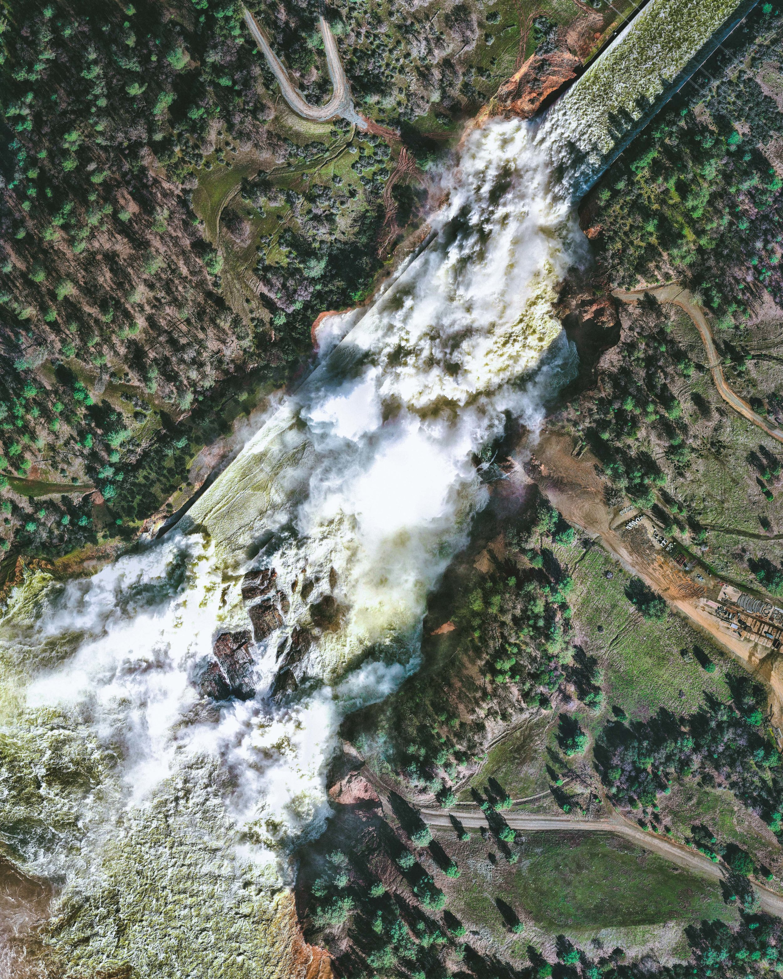 """Water rushes down the main spillway of the Oroville Dam, located on the Feather River in northern California. At 770 feet high (235m), the dam is the tallest in the United States and serves mainly for water supply, hydroelectricity generation, and flood control. Amid heavy rainfall in February 2017, this spillway was significantly damaged and more than 180,000 people living downstream were evacuated.  39°32'21.2""""N, 121°29'48.6""""W  Source imagery: Nearmap"""