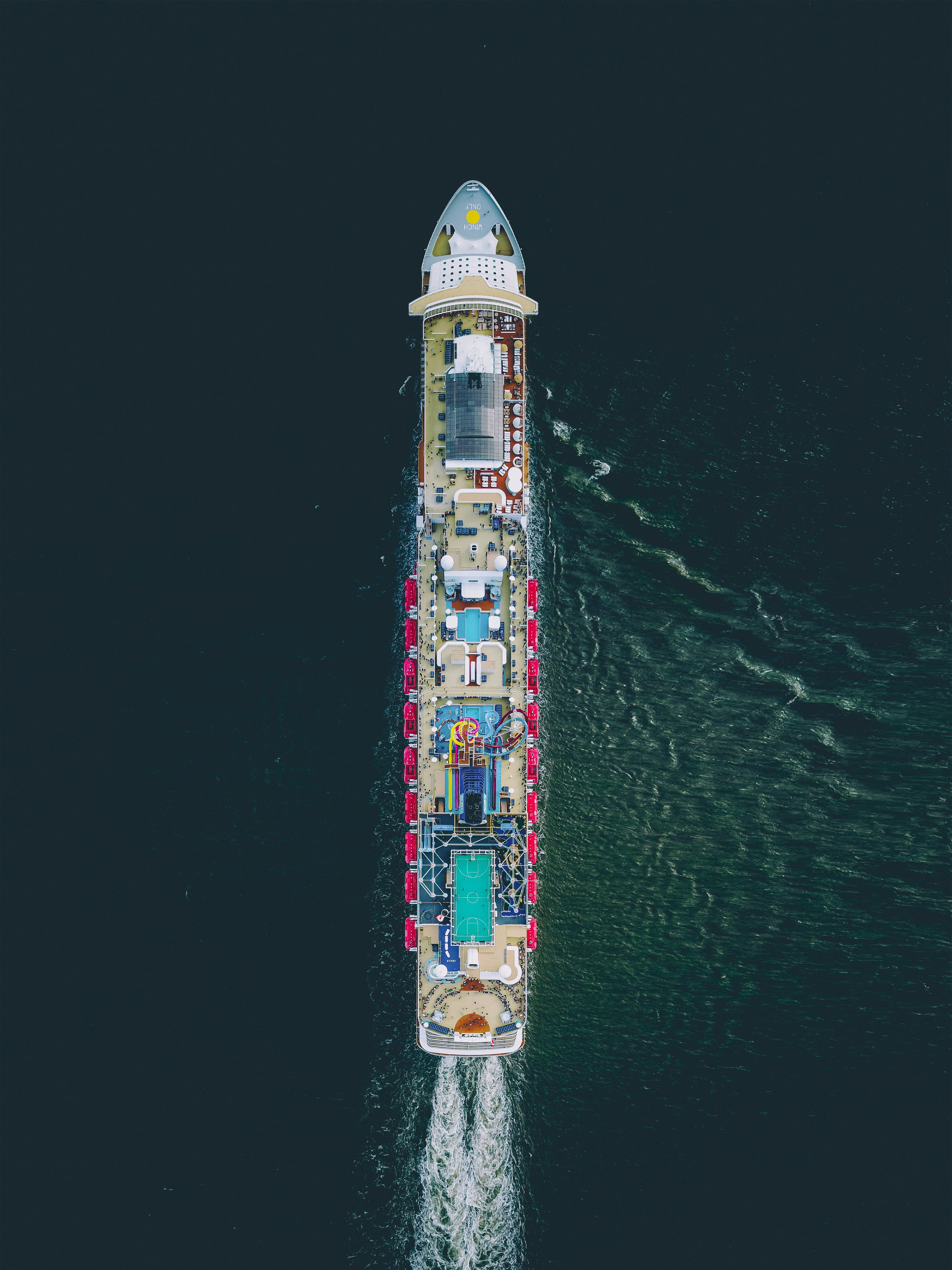 """The Norwegian Breakaway cruises through the Atlantic Ocean, en route to Bermuda from New York City. This massive ship is 1,068 feet long (325 m) and has capacity for 3,963 passengers. It has 1,024 cabins, 238 suites, several bars and restaurants, a waterpark, casino, spa, and other attractions for travelers.  36°39'15.8""""N, 69°29'53.9""""W  Source imagery: Martin Sanchez (@zekedrone)"""