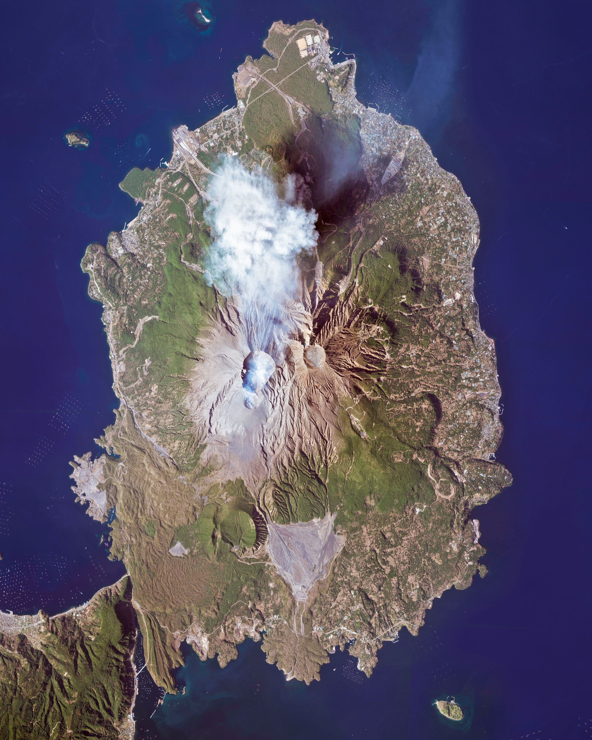 """Sakurajima is an active stratovolcano and a former island in Kyushu, Japan. Lava flows from the volcano's 1914 eruption connected it with the Osumi Peninsula, as shown in the bottom left of this Overview. Since 1955, Sakurajima has been erupting almost constantly, producing thousands of small explosions every year.  31°35'00.0""""N, 130°39'00.0""""E  Source imagery: DigitalGlobe"""