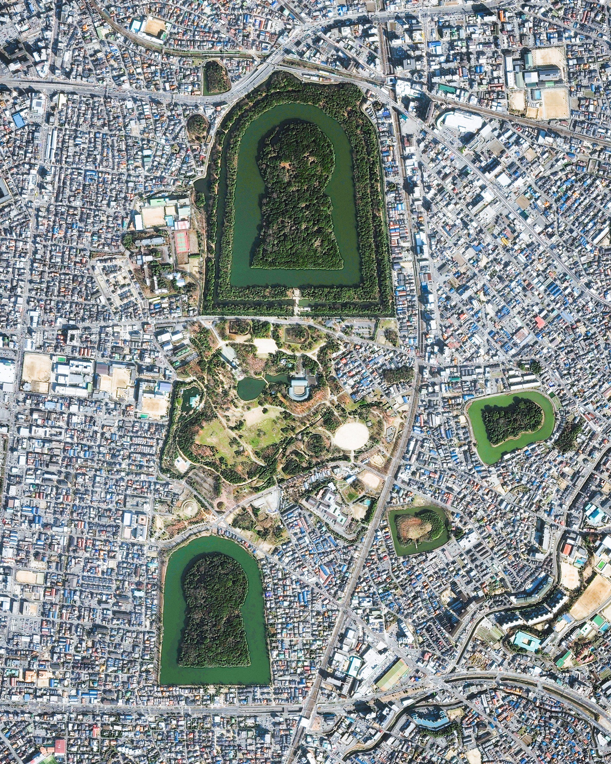 """Keyhole-shaped tumuli are scattered throughout the city of Sakai in Japan's Osaka Prefecture. A tumulus is a mound of earth or stone raised over a grave, and the largest one shown in this Overview is the final resting place of Emperor Nintoku. Nearly 1,600 feet (486 m) long with a mound 115 feet (35 m) high, it covers the largest area of any tomb in the world.  34°33'45.2""""N, 135°29'11.1""""E  Source imagery: DigitalGlobe"""