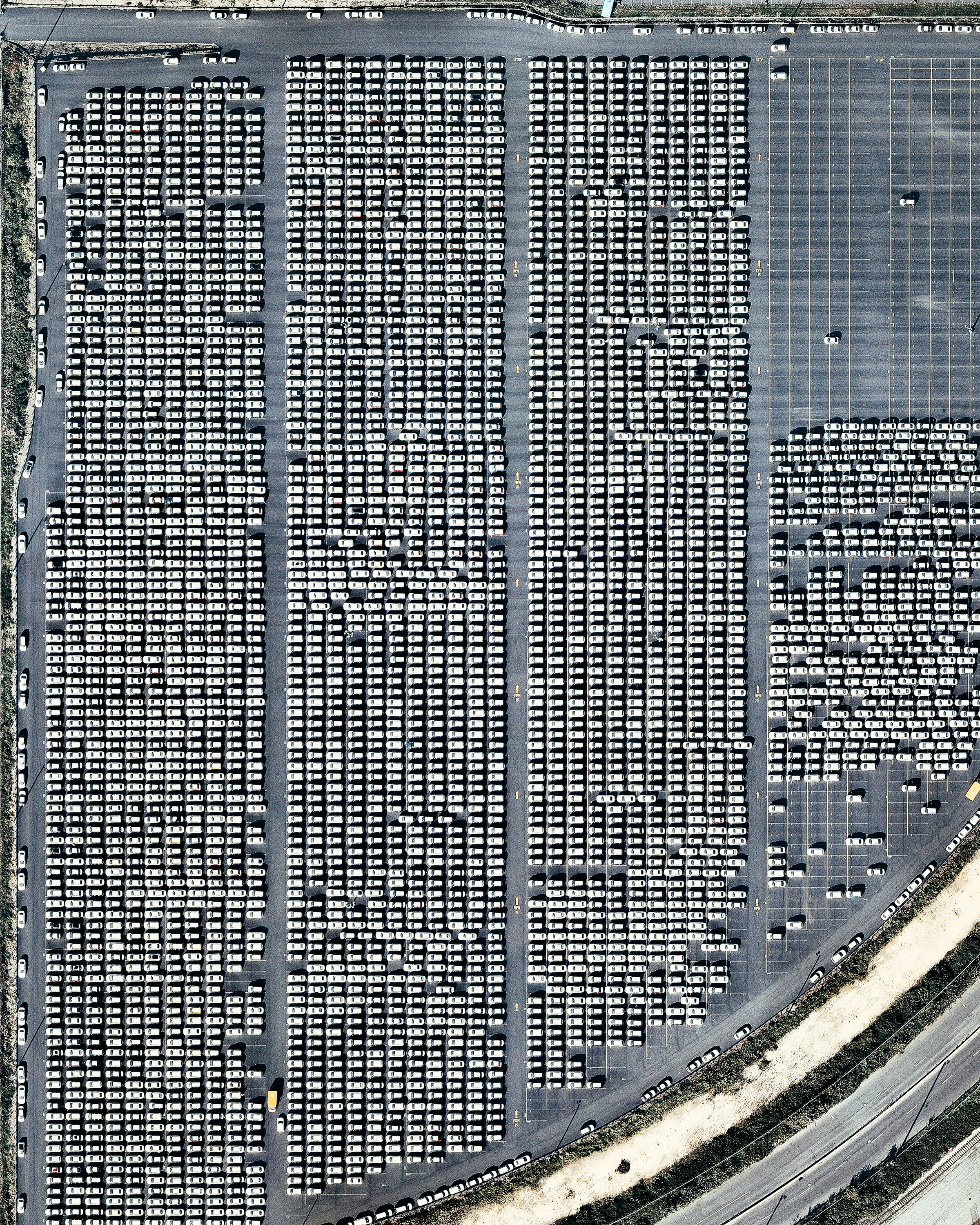 """Hundreds of vehicles are parked in a processing lot near the Port of Philadelphia, Pennsylvania. Since 2010, hundreds of thousands of Hyundai and Kia vehicles have arrived at """"PhilaPort"""" — located on the Delaware River — aboard cargo ships from South Korea. After processing, these vehicles are delivered to dealerships across the country by truck and by rail.  39°54'13.9""""N, 75°08'34.6""""W  Source imagery: Nearmap"""