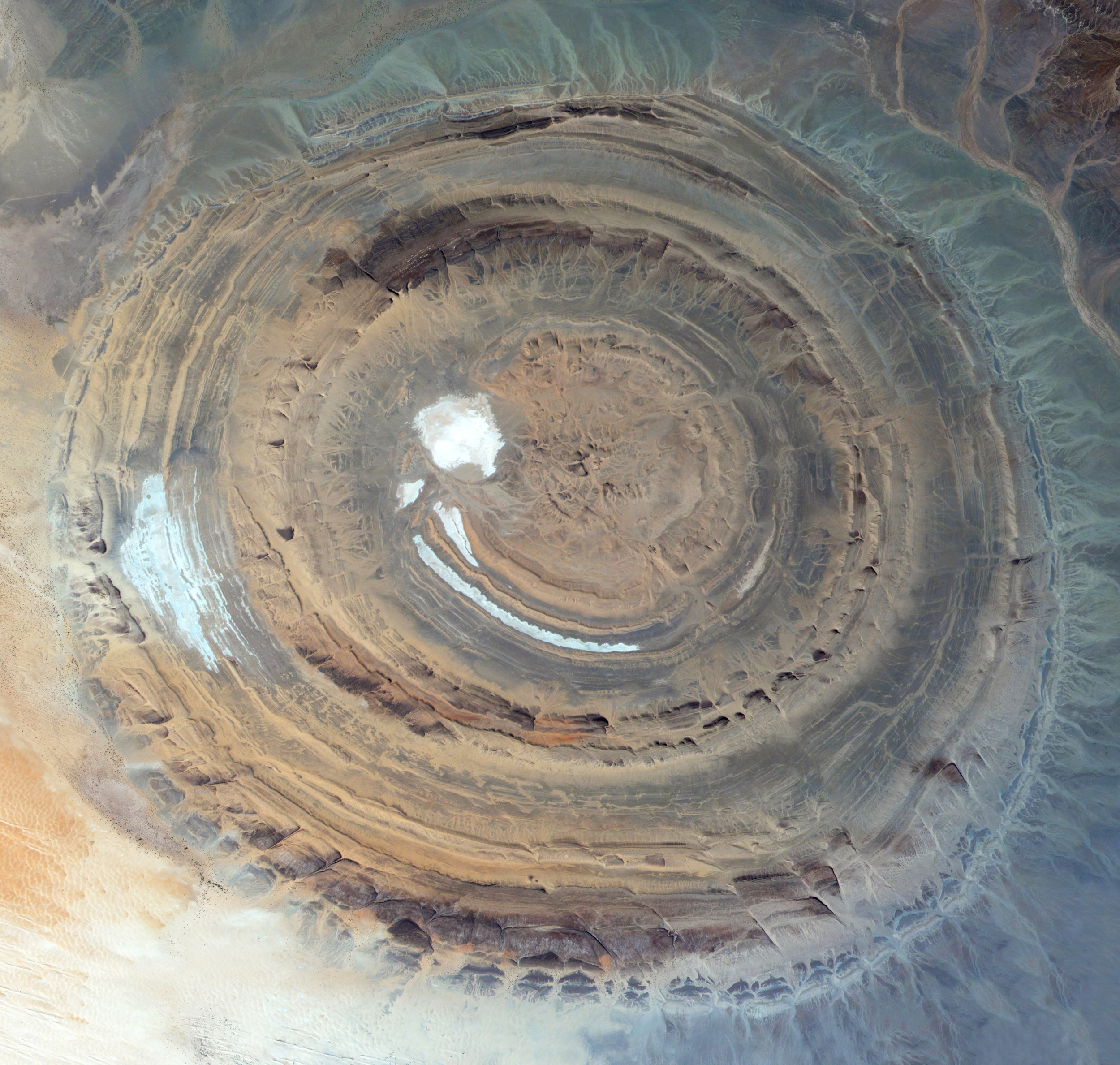 """The Richat Structure, also known as the """"Eye of the Sahara,"""" is a prominent circular feature in the Sahara Desert of west-central Mauritania. Measuring 30 miles (50 km) in diameter, the structure was originally thought to have been formed by the impact of an asteroid; however, it is now known to be an eroded structural dome of layered sedimentary rocks.  21°07'26.4""""N, 11°24'07.2""""W  Source imagery: Axelspace"""