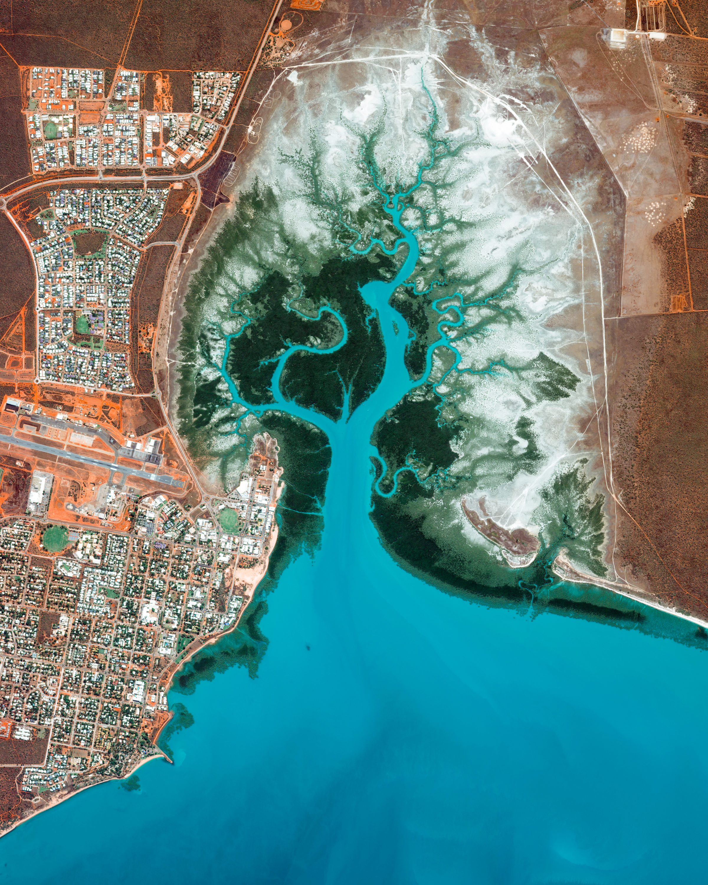 """Dampier Creek winds its way inland to form the eastern border of Broome, a coastal town in Western Australia. Broome is home to roughly 14,000 people, but its population can grow to upwards of 45,000 per month during peak tourist season from June to August. Its 14-mile (22-km) white-sand Cable Beach, paleontology exhibits, pearl farms, and other attractions make it a popular destination for travelers around the world.  17°57'32.4""""S, 122°14'49.8""""E  Source imagery: DigitalGlobe"""