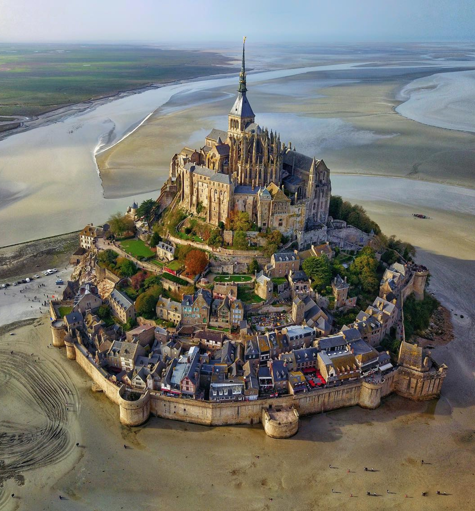 """This week's """"Drone Sunday"""" post from From Where I Drone gives us an incredible view of Mont St. Michel in Normandy, France. Over the past 600 years, the island has functioned as a prominent monastery (accessible to pilgrims only during low tide), a French military fortification, and a prison. Follow From Where I Drone for more incredible drone photos!  48°38'09.6""""N, 1°30'41.0""""W  Source imagery: @secretagent_wesanderson"""