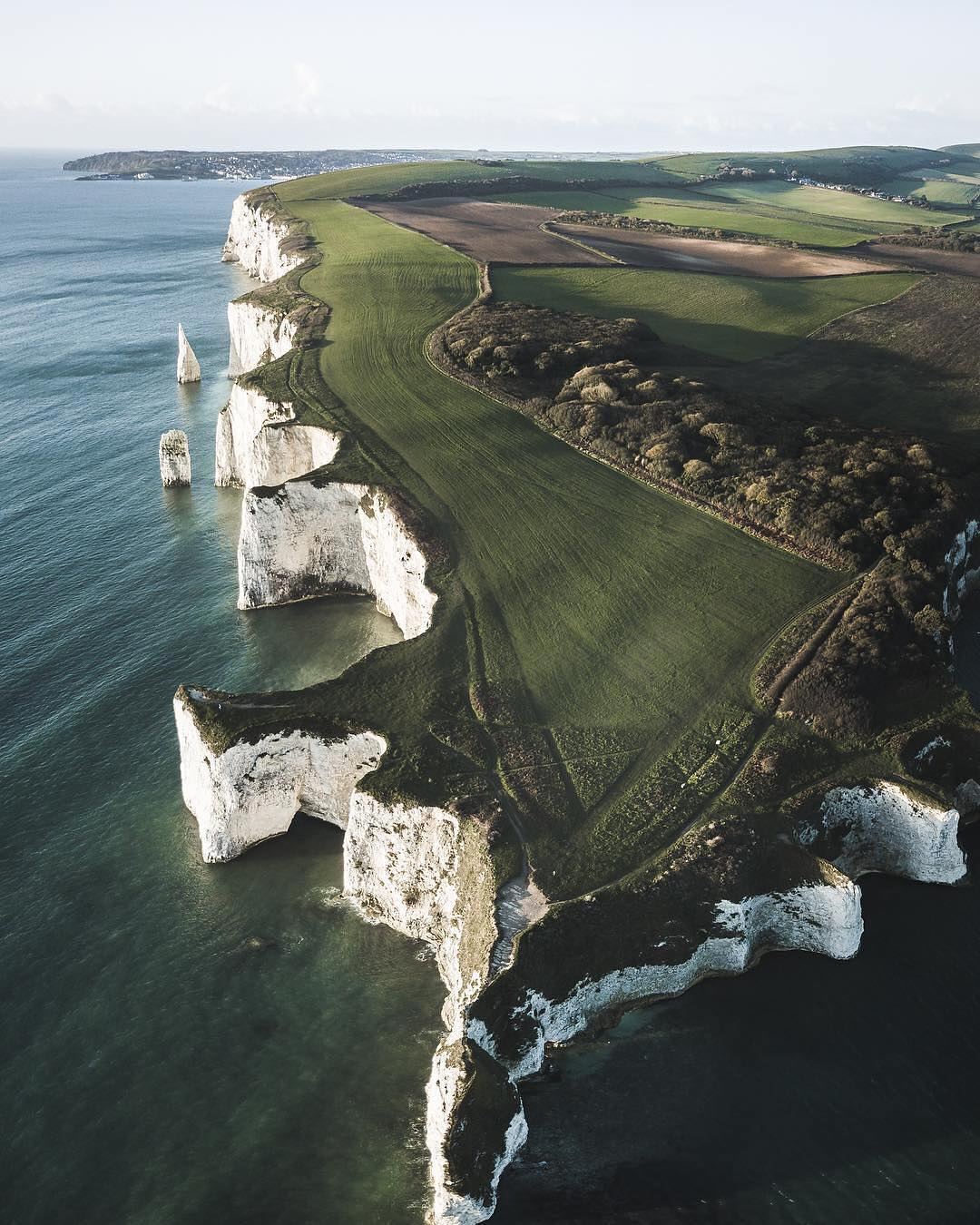 """Check out this week's """"Drone Sunday"""" post from From Where I Drone, which gives us an amazing view of Old Harry Rocks, a unique formation of chalk cliffs on the Isle of Purbeck in Dorset, southern England. These rocks were formed approximately 66 million years ago, and have been gradually eroded over centuries, leaving behind standalone columns in some places. Be sure to follow From Where I Drone for more incredible drone photos!  50°38'32.3""""N, 1°55'25.0""""W  Source imagery: Paul Watson Photography"""