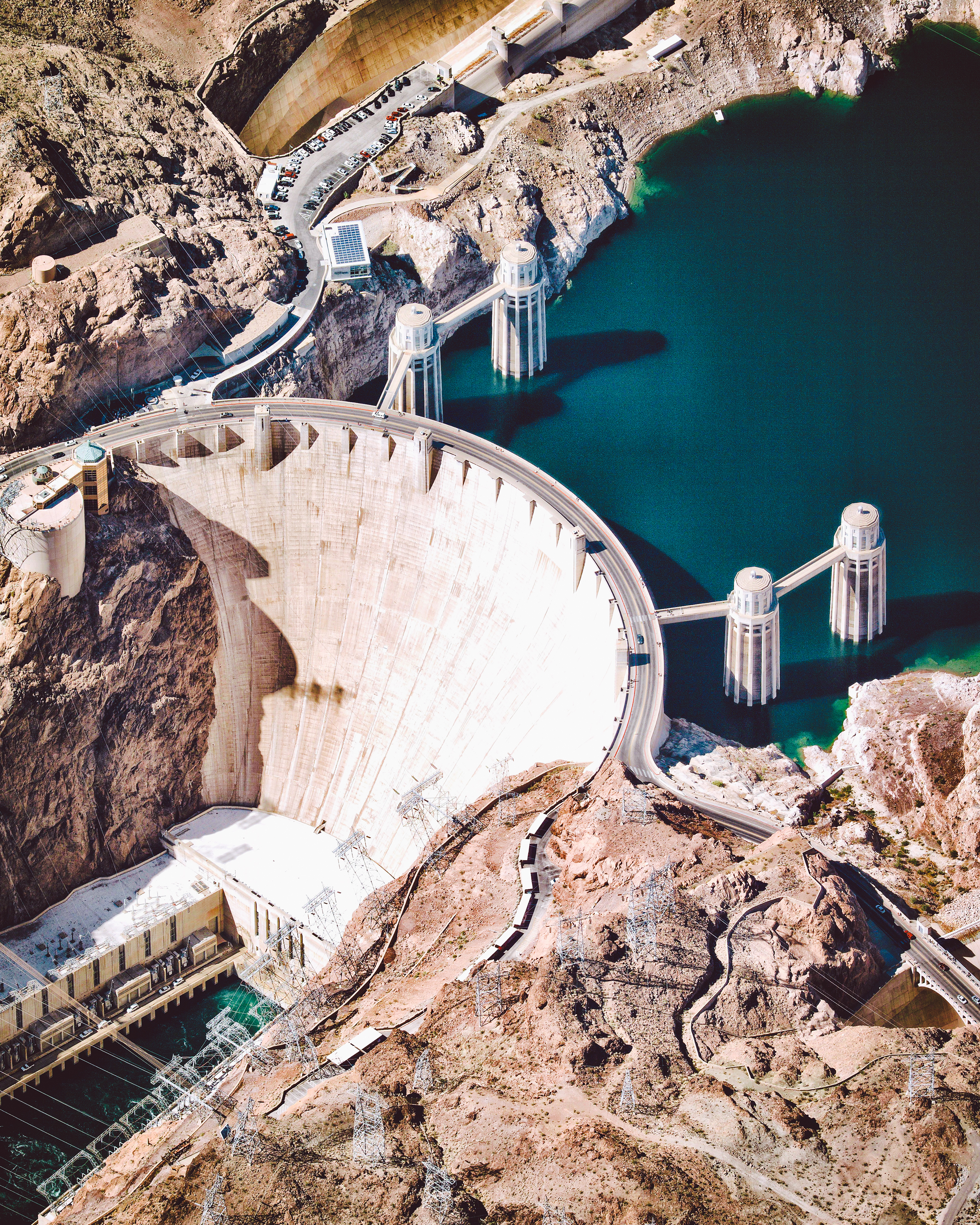 """The Hoover Dam is a concrete arch-gravity dam in the Black Canyon of the Colorado River, situated on the border of Nevada and Arizona. Standing 726.4 feet (221.4 m) tall and 1,244 feet (376 m) long, it impounds Lake Mead, the largest reservoir in the United States by volume. Construction of the Hoover Dam between 1931 and 1936 served as a massive public works project of the Great Depression, employing thousands of workers — in fact, when the dam was authorized, nearly 20,000 unemployed individuals flocked to Las Vegas (a city of just 5,000 at the time) in hopes of finding work.  36°00'56.0""""N, 114°44'16.0""""W  Source imagery: Nearmap"""