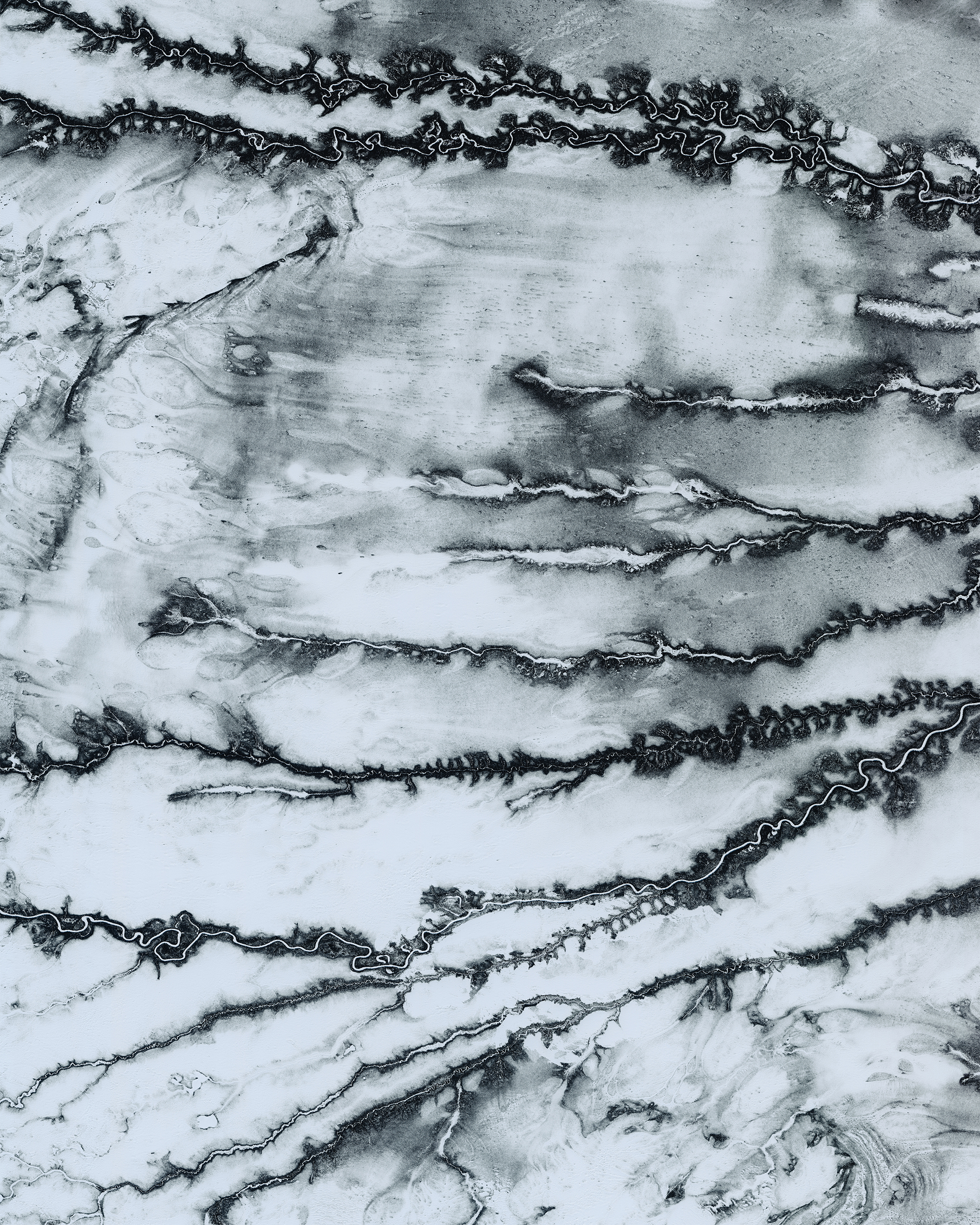 """Tributaries of the Moose River snake across snowy terrain near Moosonee, a town in northern Ontario, Canada. This area is part of the Hudson Plains Ecozone, a sparsely populated subarctic region extending from the western coast of Quebec to the coast of Manitoba. The ecozone contains the largest continuous wetland in the world, including the Moose River's 41,900-square-mile (108,500 sq. km) drainage basin.  51°04'26.3""""N, 81°28'28.6""""W  Source imagery: DigitalGlobe"""