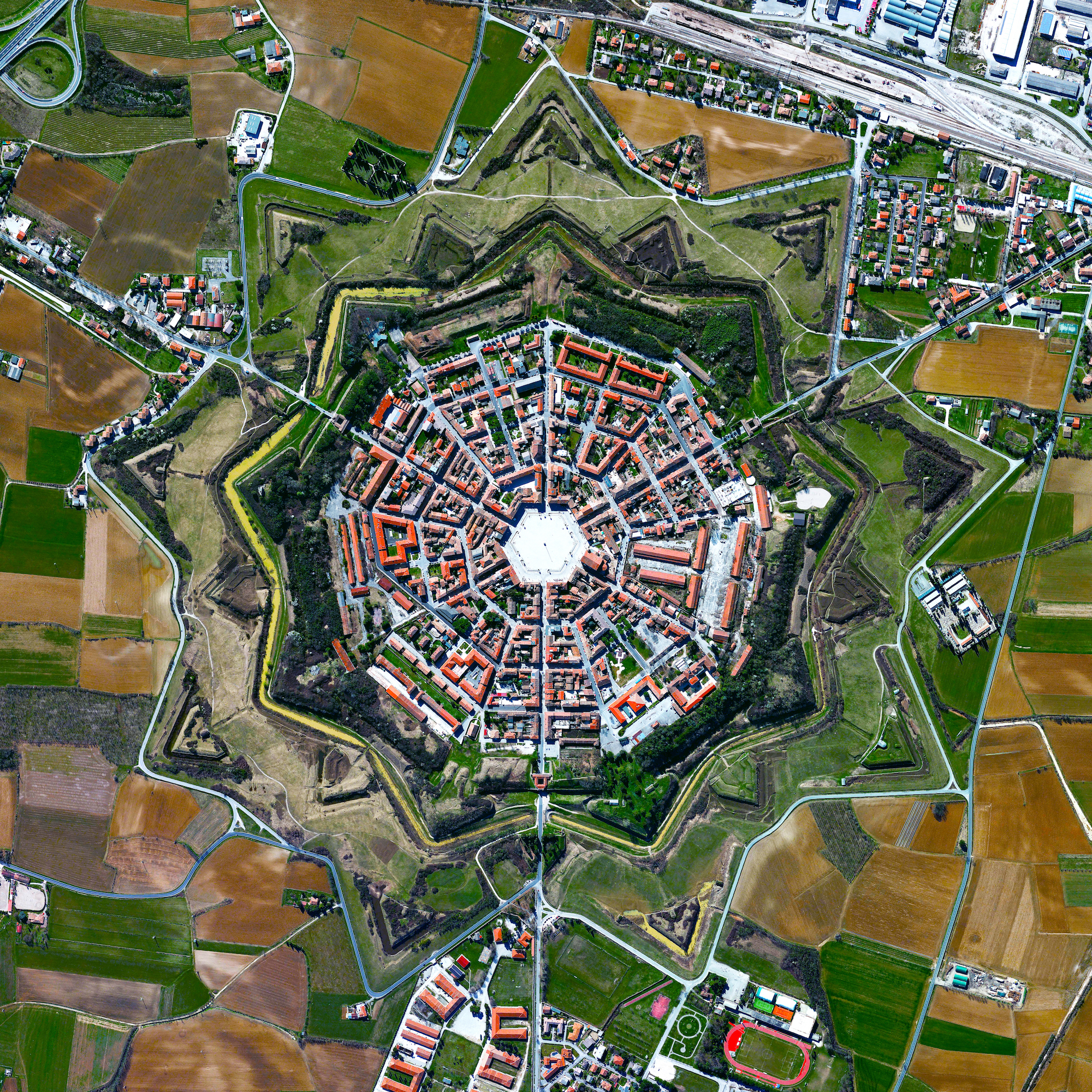"""The town of Palmanova, Italy, is recognized by its concentric layout known as a """"star fort."""" The rationale for this construction was that an attack on any individual wall could be defended from the two adjacent star points by shooting the enemy from behind. The three rings that surround Palmanova were completed in 1593, 1690, and 1813.  45°54'17.8""""N, 13°18'35.8""""E  Source imagery: DigitalGlobe"""