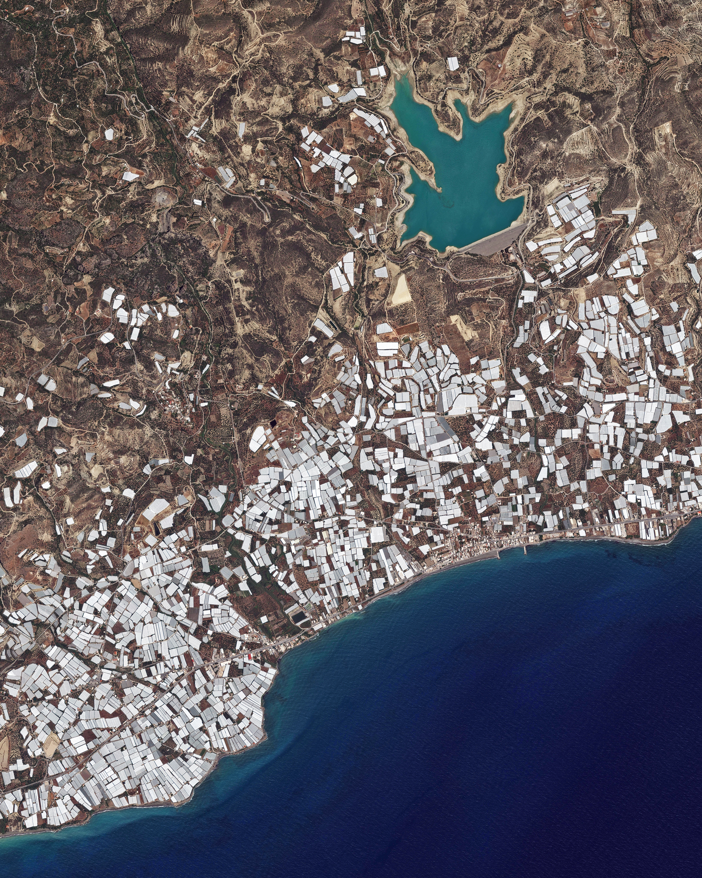 """Plastic greenhouses cover a stretch of shoreline on the south coast of Crete — the largest and most populous of the Greek islands. Inside these greenhouses, which cover an area of roughly 6 square miles (15 sq. km), large quantities of fruits and vegetables are grown for export. In the upper right corner of this Overview is the Bramiana Reservoir, which was built in 1986 to meet the needs of the thousands of greenhouses surrounding it.  35°01'45.4""""N, 25°41'46.0""""E  Source imagery: DigitalGlobe"""