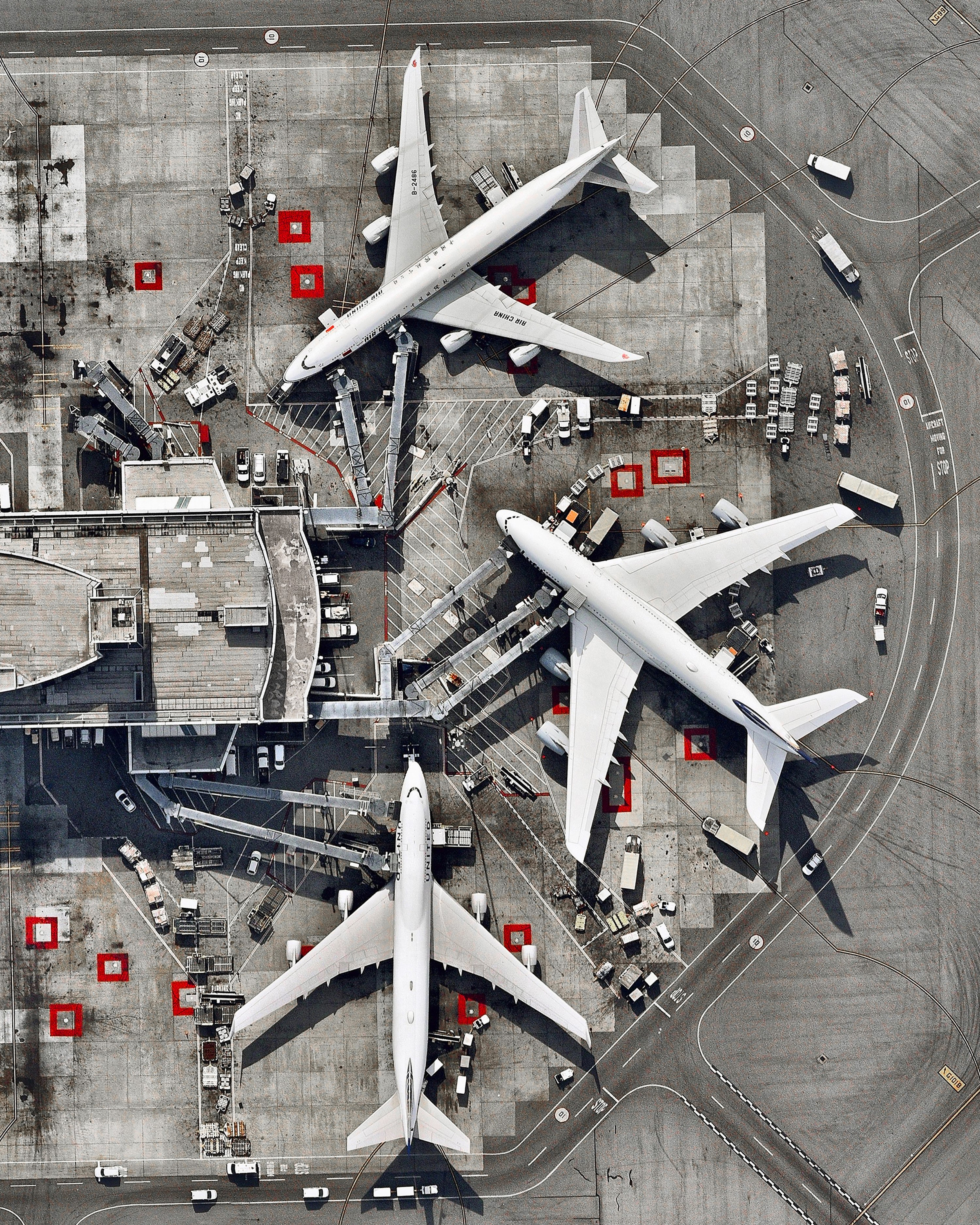 """Three massive airplanes are docked at San Francisco International Airport in California, USA. SFO is the 21st busiest airport in the world by passenger traffic, accommodating more than 50 million passengers each year.  37°37'07.2""""N, 122°23'35.8""""W  Source imagery: Nearmap"""