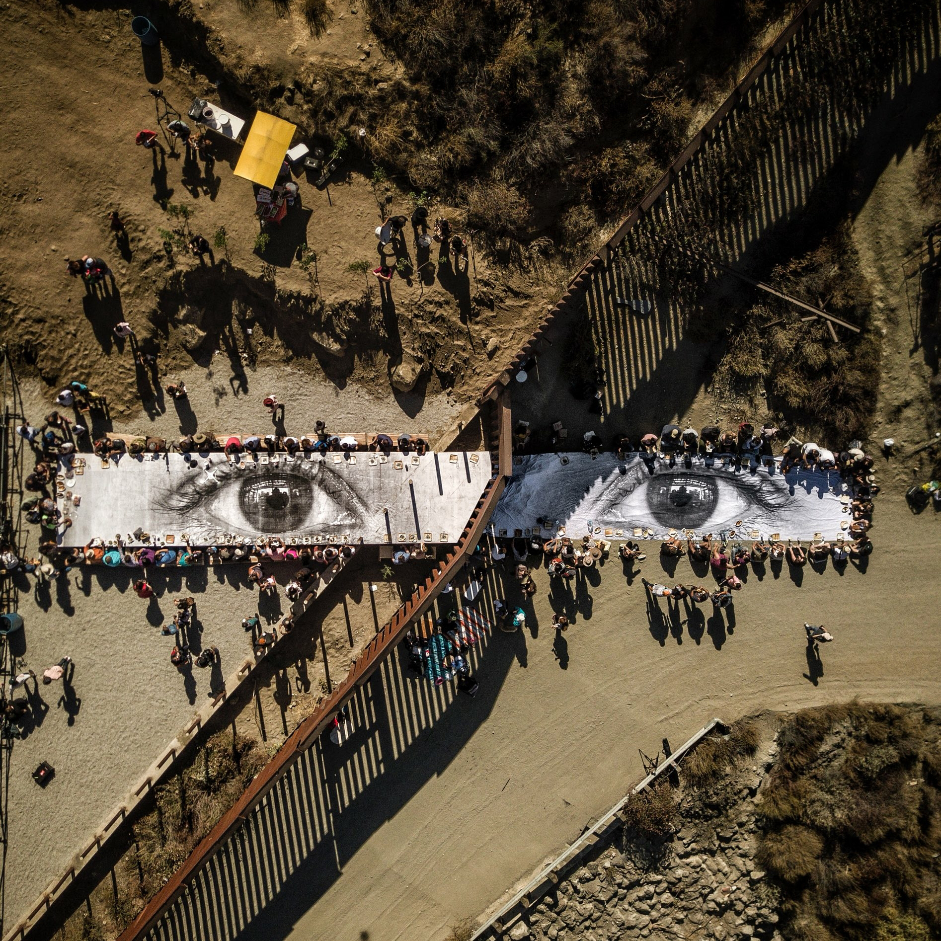 """This Overview shows a large picnic at US-Mexico border, spanning from Tecate, California, USA, to Tecate, Baja California, Mexico. The meal is being eaten atop """"the eyes of a Dreamer,"""" a mural painted by French artist """"JR"""" for the one-day-only installation in October 2017. The eyes depicted in the mural are those of a Deferred Action for Childhood Arrivals (DACA) recipient.  32°34'34.1""""N, 116°37'45.8""""W  Source imagery: JR"""