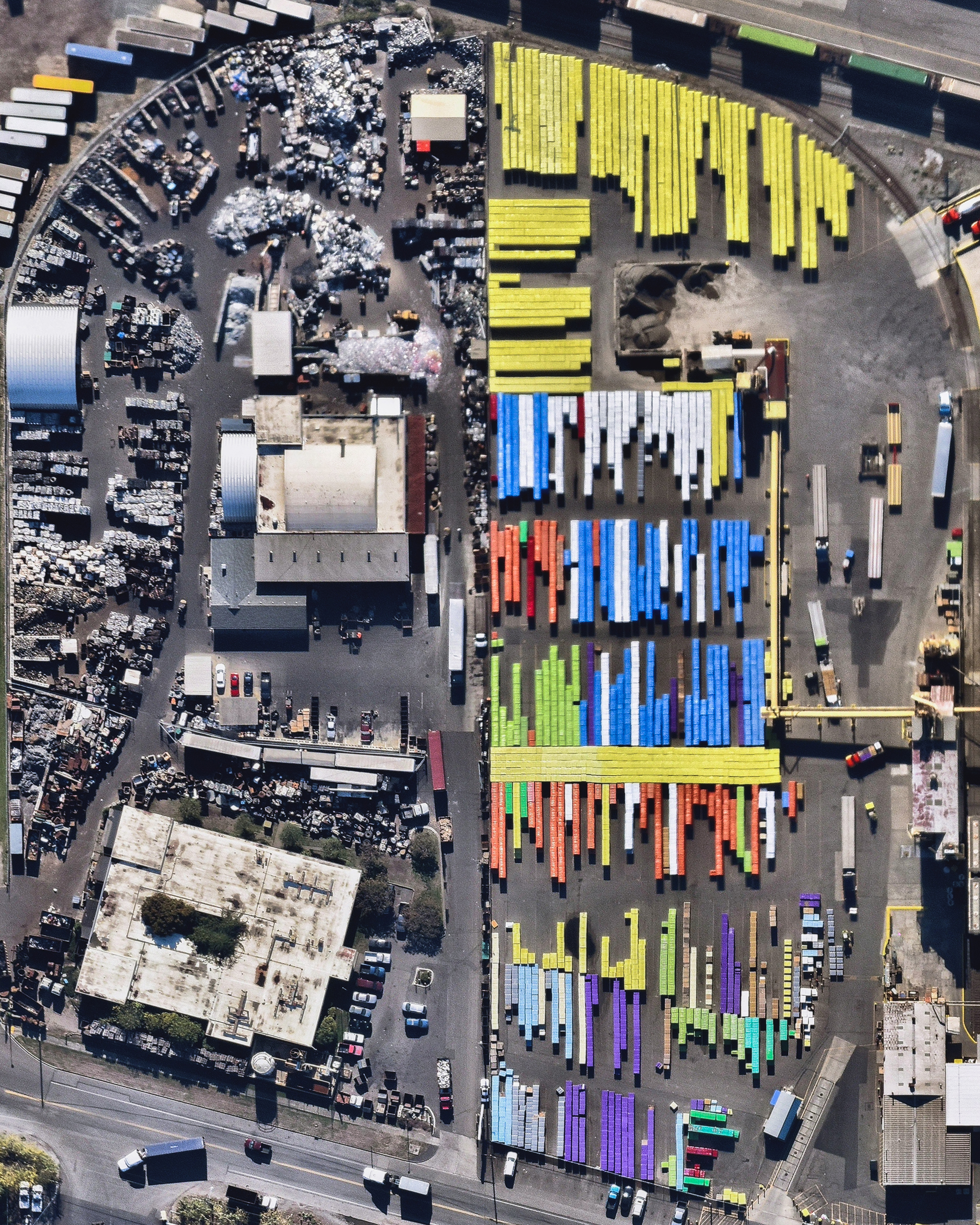 "Brightly colored shipping containers are stacked next to a scrap metal storage yard at the Port of Tacoma, Washington. This facility takes in a variety of scrap metals from commercial, industrial and public sources throughout the Pacific Northwest and then sorts, packages and ships it to recycling plants, mills and foundries around the world. In 2015, the Port of Tacoma handled $52.1 billion in international trade, importing and exporting 19 million short tons of cargo.  47°15'33.5""N, 122°24'20.2""W  Source imagery: Nearmap"