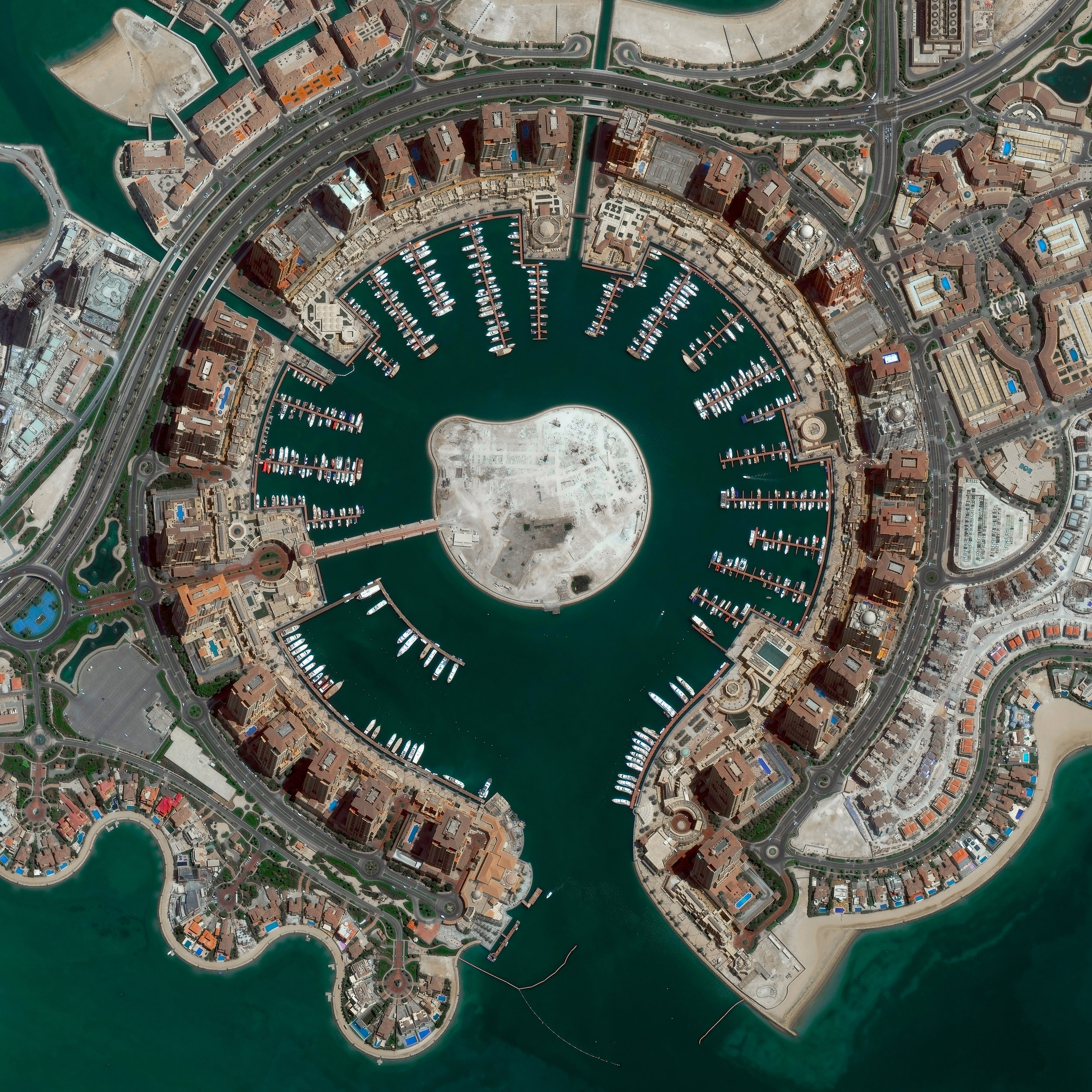 """The Pearl-Qatar is an artificial island in Doha, Qatar, spanning nearly 2.5 miles (4 km) in the Persian Gulf. Once completed, the island is expected to have nearly 19,000 dwellings and 45,000 residents. Twelve precincts make up the Pearl-Qatar, and each one has a national or international theme — including aspects of Arabic, Mediterranean and European culture.  25°22'07.0""""N, 51°33'07.0""""E  Source imagery: DigitalGlobe"""