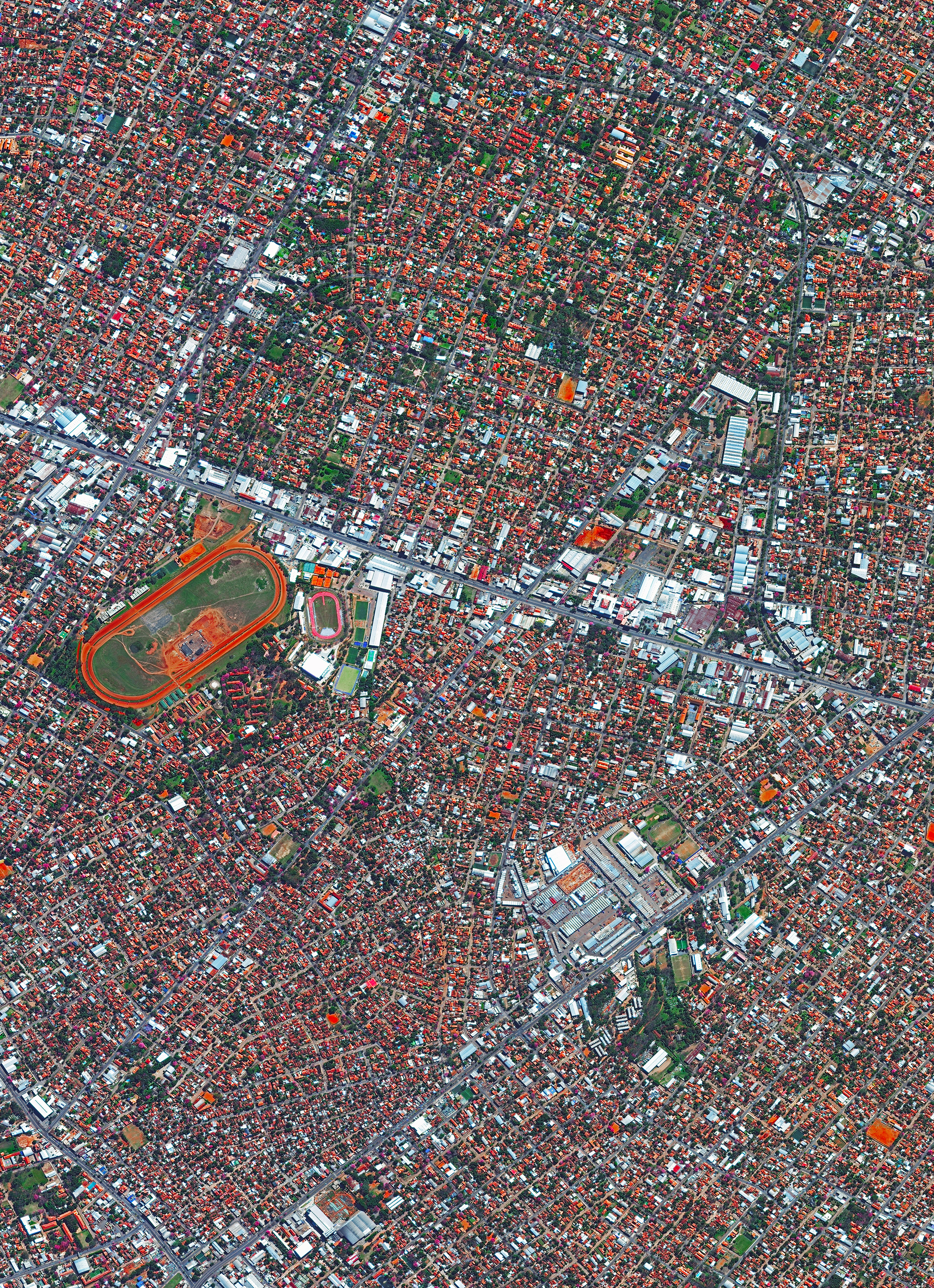 """Asunción is the capital and largest city of Paraguay, with nearly 2.2 million people living in its metropolitan area. Known as """"the Mother of Cities,"""" it is one of the oldest cities in South America and the longest continually inhabited area in the Río de la Plata Basin. Shown on the left side of this Overview is the Hipódromo de Asunción, an 80,000-seat horse racing track and popular concert venue.  25°18'00.0""""S, 57°38'00.0""""W  Source imagery: DigitalGlobe"""