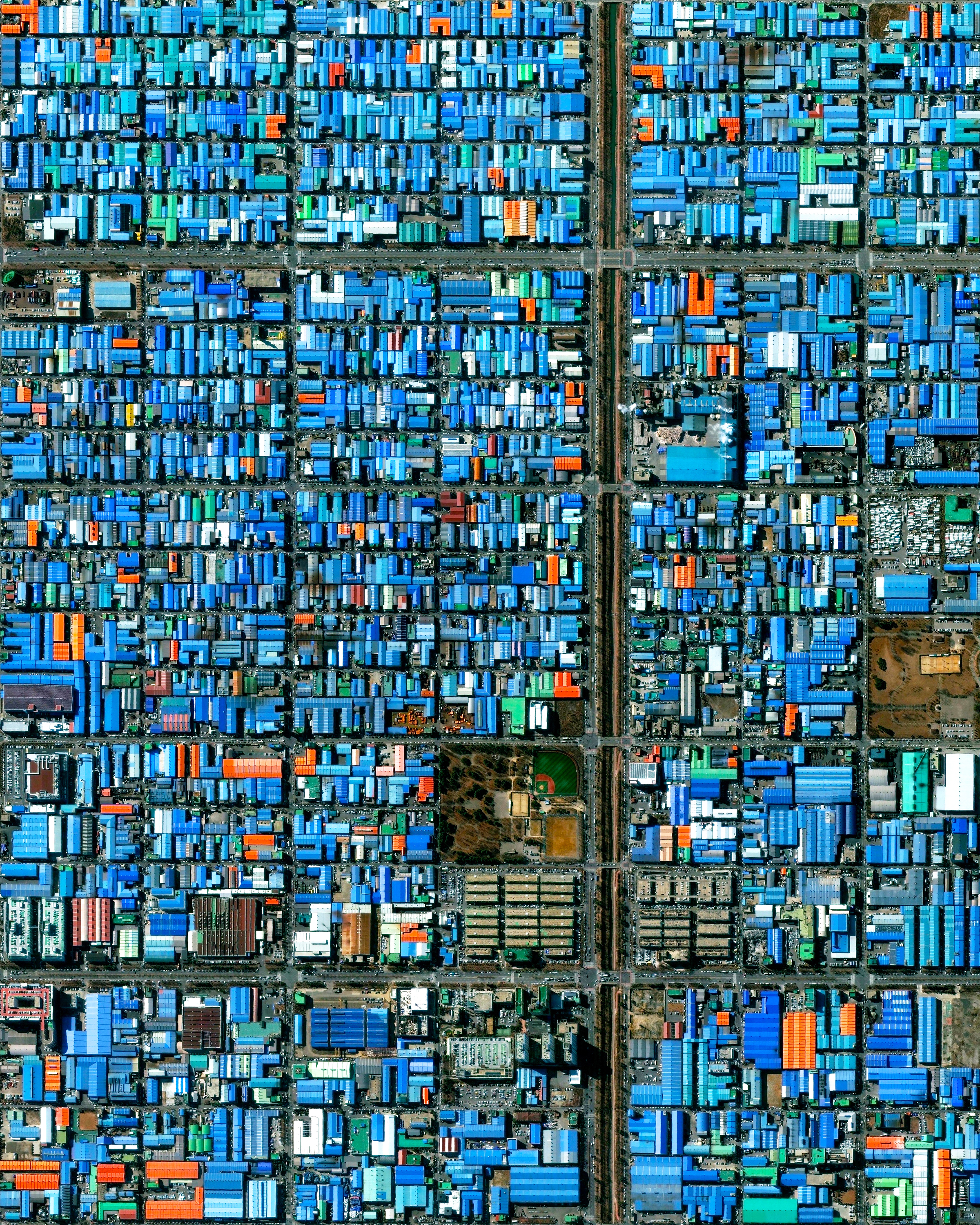 """This Overview captures Jeongwang-dong, an industrial sector in the city of Ansan, South Korea. The Korean government has intensively driven development of Ansan, particularly in this area, with an emphasis on manufacturing. The striking blue color shown here results from the use of aluminum roofing, which is used for its low cost and longevity.  37°20'22.0""""N, 126°42'54.9""""E  Source imagery: DigitalGlobe"""