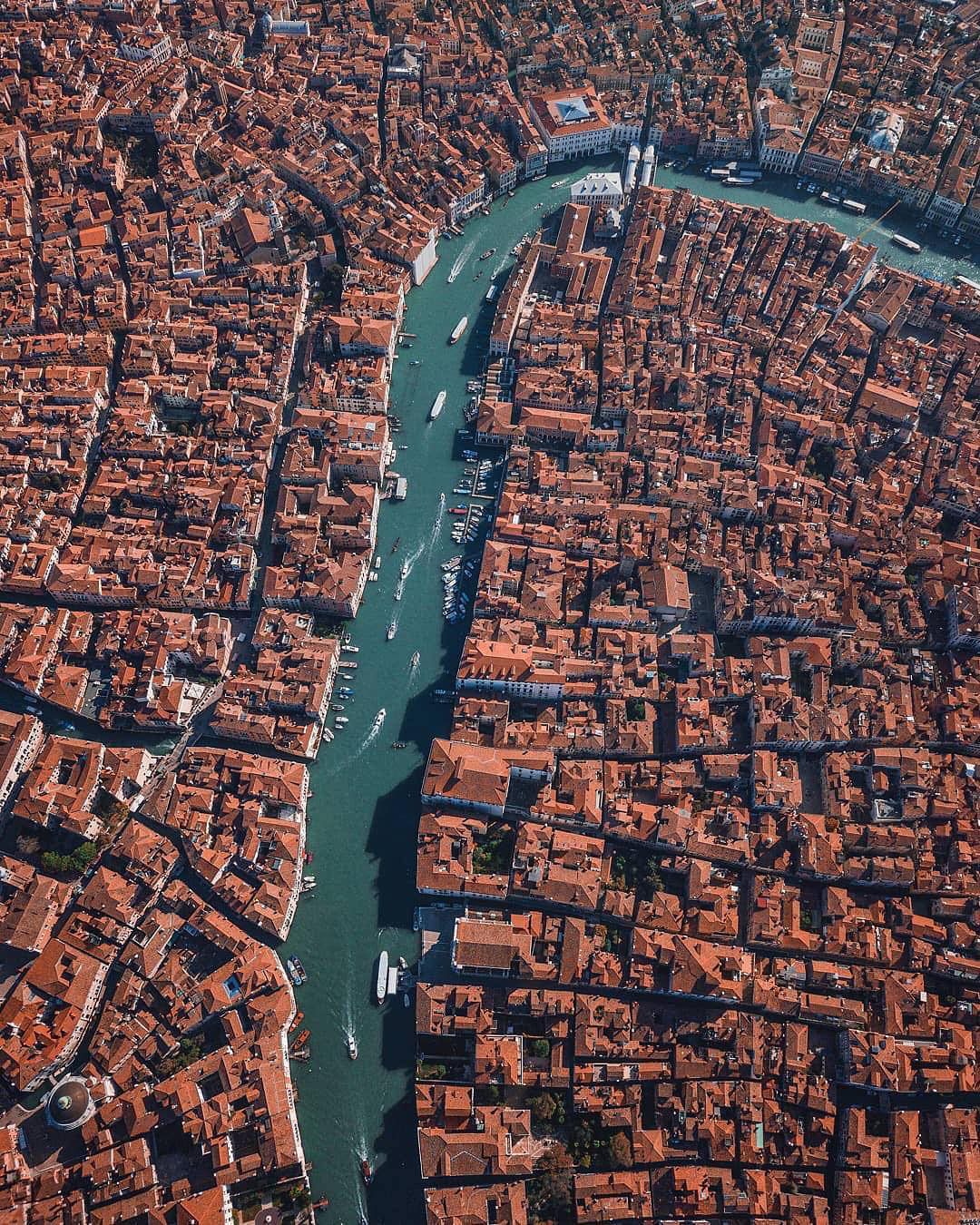 """Check out this awesome shot of the Grand Canal flowing through Venice, Italy. One of the major water-traffic corridors in the city, the Grand Canal is 2.4 miles (3.8 km) long, between 98 and 295 feet (30-90 m) wide, and has an average depth of 16 feet (5 m). Near the top of this image — where the canal bends — we can see the famous Ponte di Rialto, a 16th-century stone pedestrian bridge and major Venetian tourist attraction.  45°26'21.2""""N, 12°20'09.2""""E  Source imagery: Sebastien Nagy"""