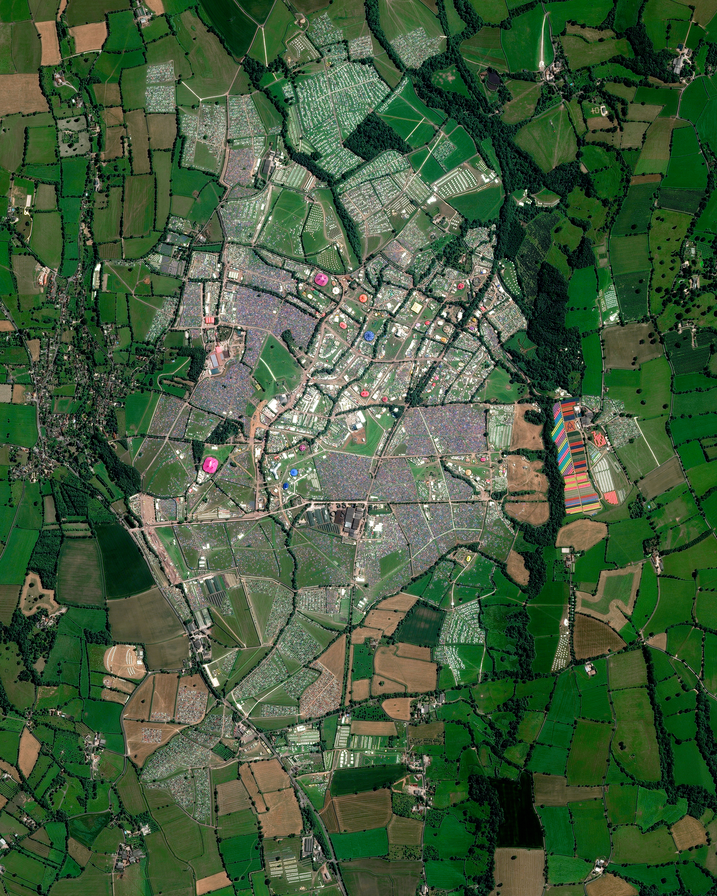This Overview captures the 2017 Glastonbury Festival in Pilton, England. The annual, five-day music event was attended by more than 135,000 people. Concert-goers are provided a campsite at the venue but must bring their own tents — which vividly dot the landscape in this Overview. The population of Pilton on the other 360 days of the year is 998.  51.152500°, -2.589722°  Source imagery: Maxar Technologies