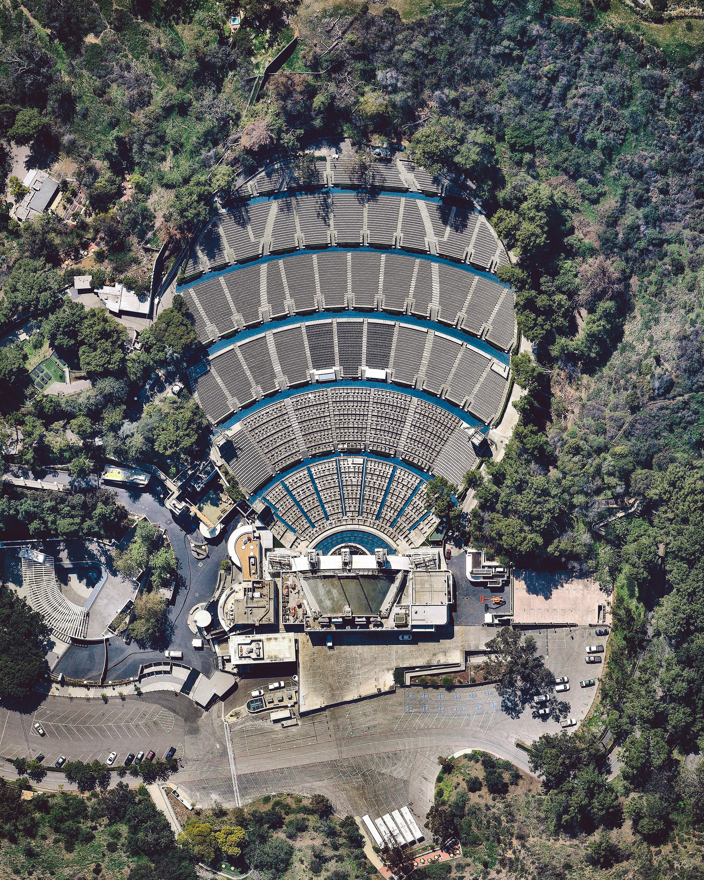"""The Hollywood Bowl is an amphitheater in the Hollywood Hills neighborhood of Los Angeles, California. The """"bowl"""" refers to the shape of the concave hillside that the theater is carved into. It was named one of the 10 best live music venues in America by Rolling Stone Magazine in 2018 and has hosted countless music legends, including Nat """"King"""" Cole, The Beatles, Elton John, Cher, and Prince.  34.112778°, -118.338889°  Source imagery: Nearmap"""