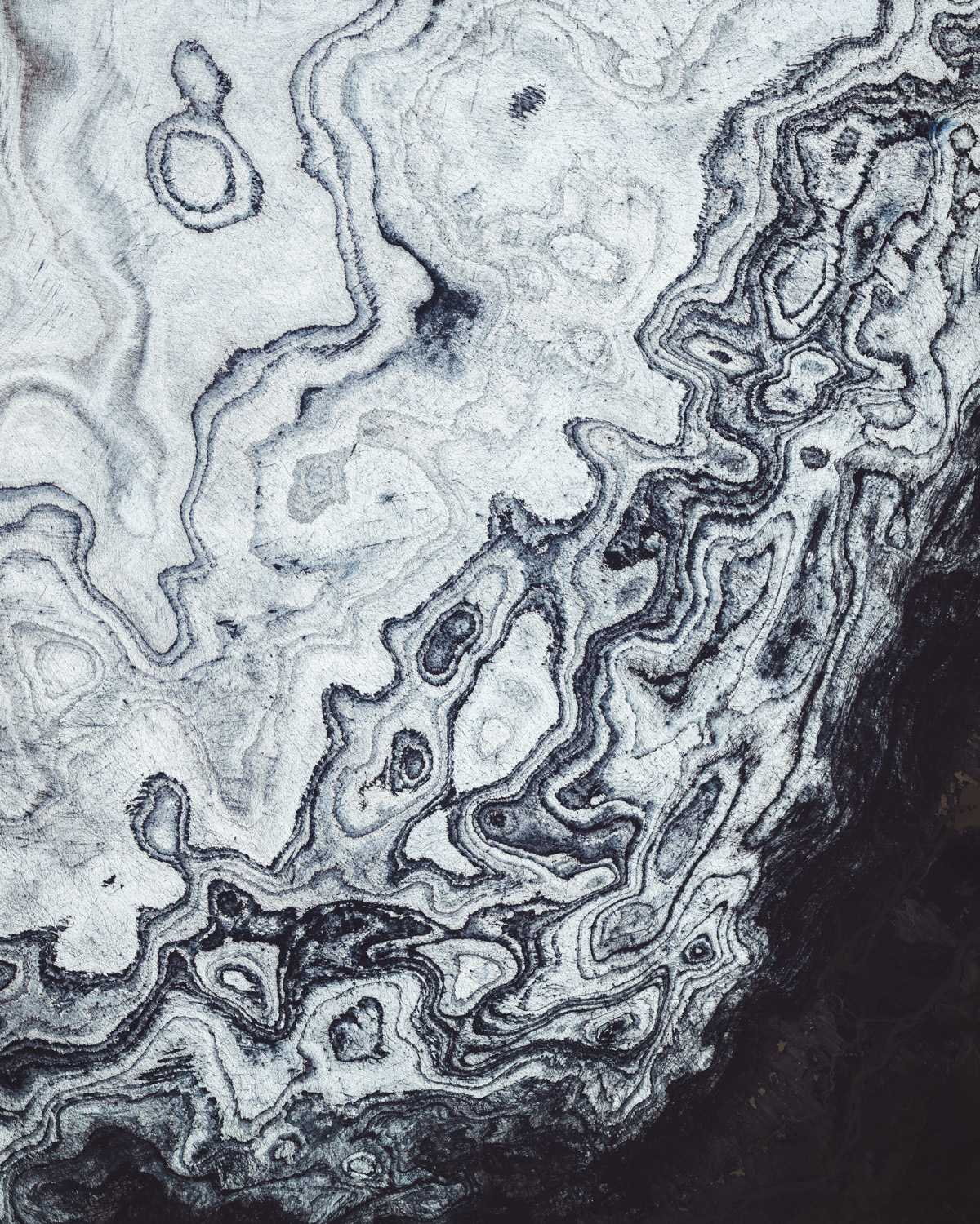 Glacial ice and volcanic sediment form contrasting patterns along the southwestern rim of Vatnajökull Glacier in Iceland. Vatnajökull is the largest and most voluminous ice cap in Iceland, covering an area of 3,100 square miles (7,900 square km) — roughly 8% of the country's total landmass. Underneath it are several volcanoes, many of which continue to erupt and can burst weakened ice, leading to glacial lake outburst floods and landslides.  64.130241°, -17.978260°  Source imagery: Maxar Technologies