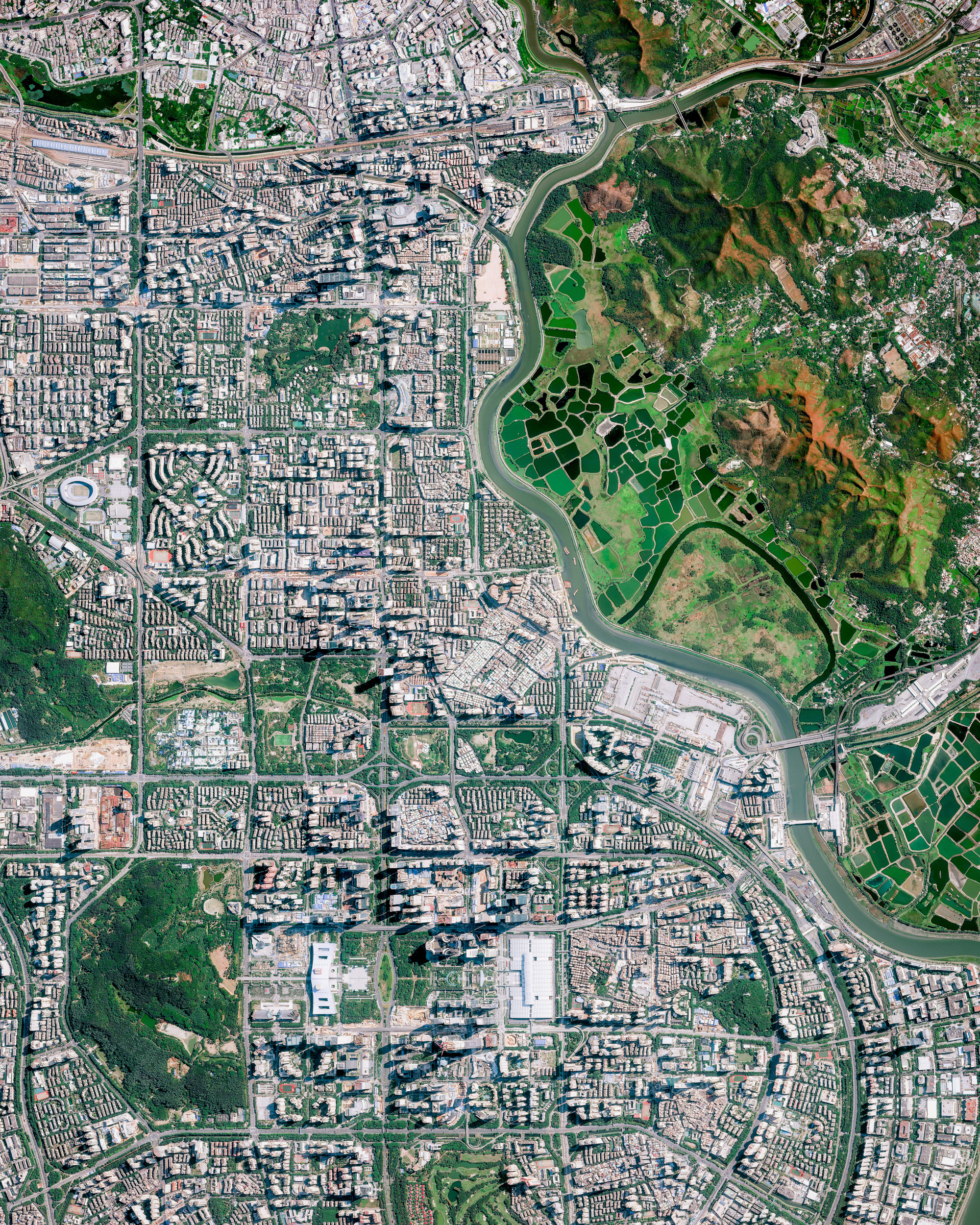 Shenzhen, China, was one of the fastest-growing cities in the world in the 1990s and 2000s and currently has a population of at least 12.5 million. Bordering Hong Kong to the south, Huizhou to the northeast, and Dongguan to the northwest, it is part of the Pearl River Delta megalopolis — one of the most densely urbanized regions in the world. Recently, along Shenzhen's border with Hong Kong, hundreds of Chinese security officers have gathered in a show of force as tensions rise between Hong Kong and mainland China.  22.550000°, 114.100000°  Source imagery: Maxar Technologies