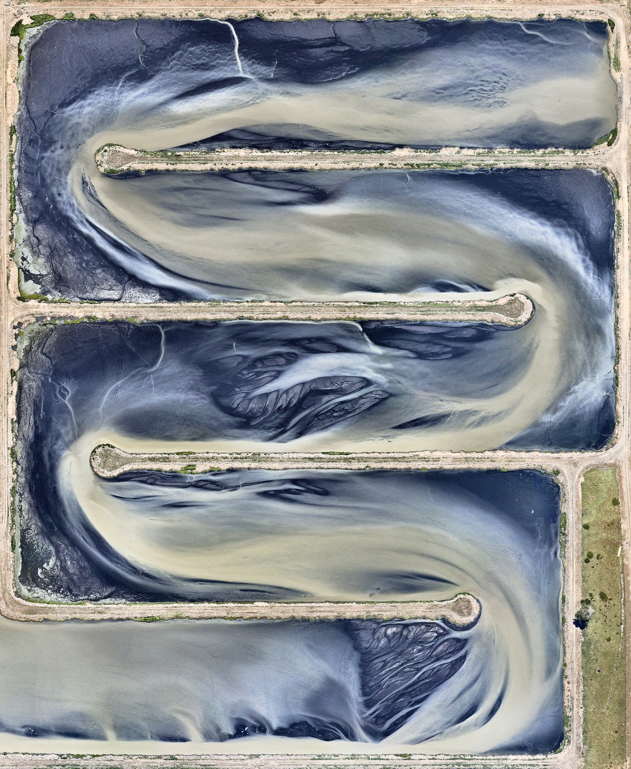 A sewage treatment pond is seen at the Western Treatment Plant in Cocoroc, Australia. This facility treats half of the sewage produced in the nearby city of Melbourne and is nearly 26,000 acres (10,500 hectares) in size — roughly equal to the total area of Disney World. The Western Treatment Plant produces 10.5 billion gallons (40 billion liters) of Class A water, the highest standard of recycled water.  -37.985213°, 144.609568°  Source imagery: Nearmap