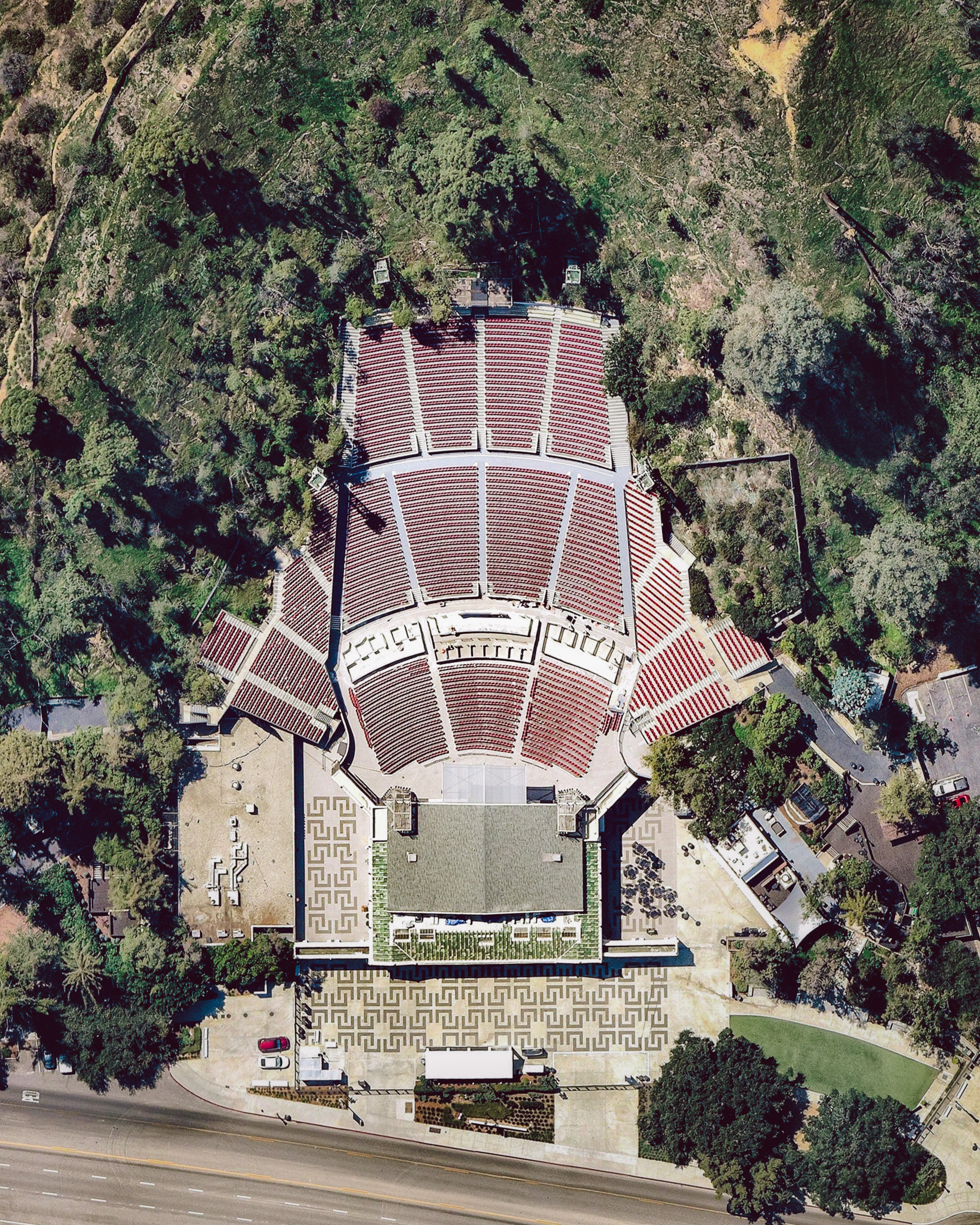 Greek Theatre is a 5,870-seat music venue in Griffith Park, Los Angeles, California. The venue hosted its first show in June 1931, selling seats in the first two sections for a dollar a piece and giving the remaining seats away for free. Since then, it has featured some big names in music — including Elton John, Aretha Franklin, Frank Sinatra, Bruce Springsteen and Carlos Santana.  34.119702°, -118.296065°  Source imagery: Nearmap