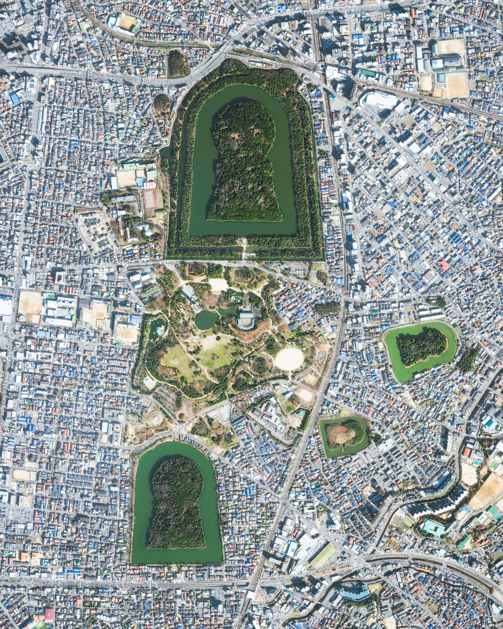 Keyhole-shaped tumuli are scattered throughout the city of Sakai in Japan's Osaka Prefecture. A tumulus is a mound of earth or stone raised over a grave, and the largest one shown in this Overview is the final resting place of Emperor Nintoku. Nearly 1,600 feet (486 m) long with a mound 115 feet (35 m) high, it covers the largest area of any tomb in the world.  34.562556°, 135.486417°  Source imagery: Maxar Technologies