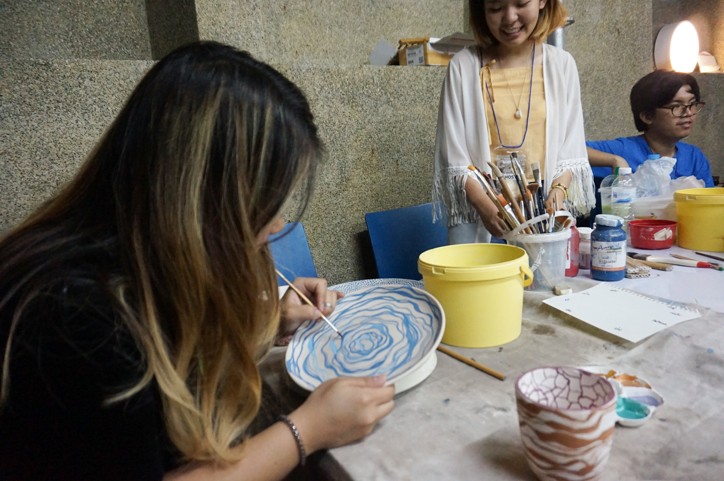 """Earn is painting her 8"""" stoneware plate."""