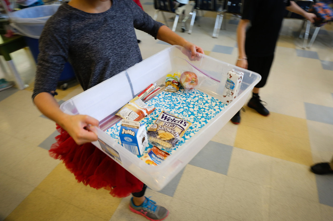 After every lunch period student volunteers carry food collected for the Food Bus program over to a designated refrigerator. Victoria Milko/NPR