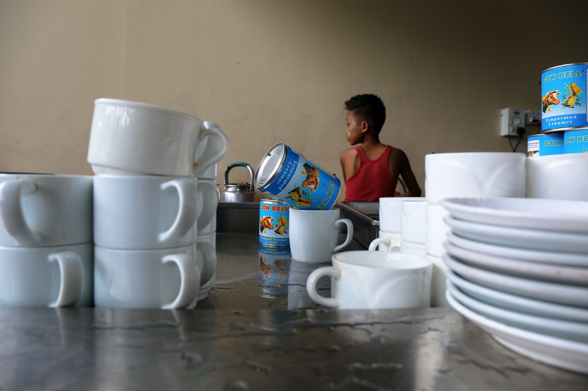 A tea shop worker does dishes at Morning Star in Tamwe, Yangon. November 2017
