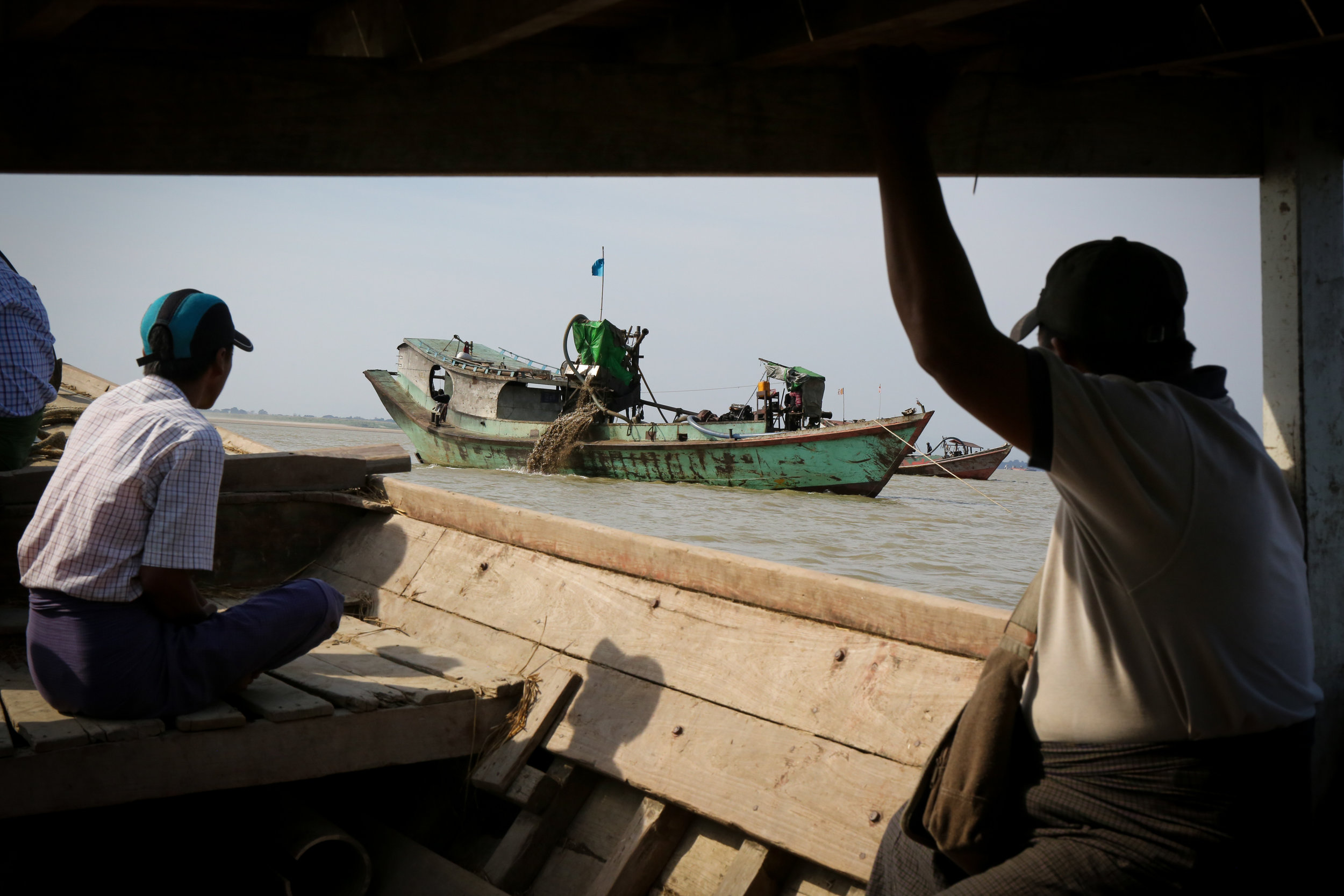 Fishermen and villagers watch a sand mining boat off the coast of their village.