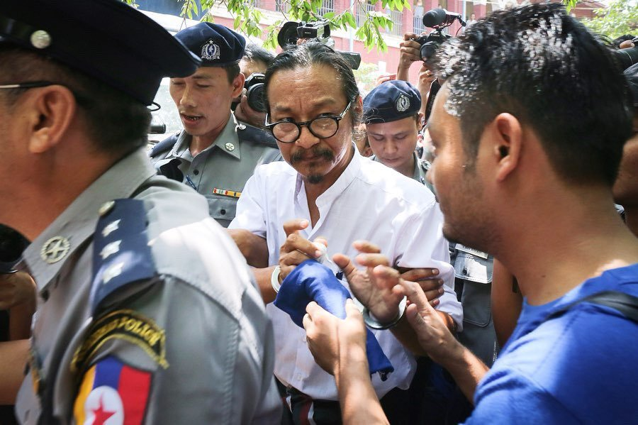 Former political prisoner Maung Saungkha hands a blue shirt to Min Htin Ko Ko Gyi as he faces trial for criticizing the military.