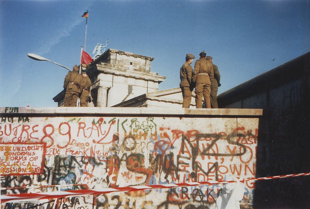 Soldiers standing on top of the Berlin Wall on Nov. 16, 1989. Image from Wikimedia Commons.
