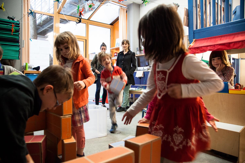 Des enfants jouent sous le regard de leurs mères venues les déposer. École aujourd'hui, Paris.  Commande pour Télérama.