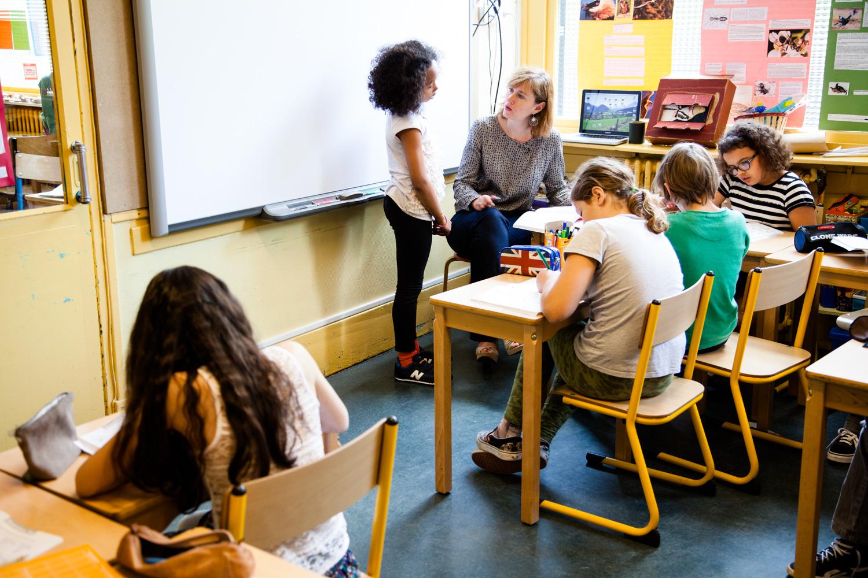 Des écoliers montrent leurs travaux à la maîtresse. École aujourd'hui, Paris.  Commande pour Télérama.