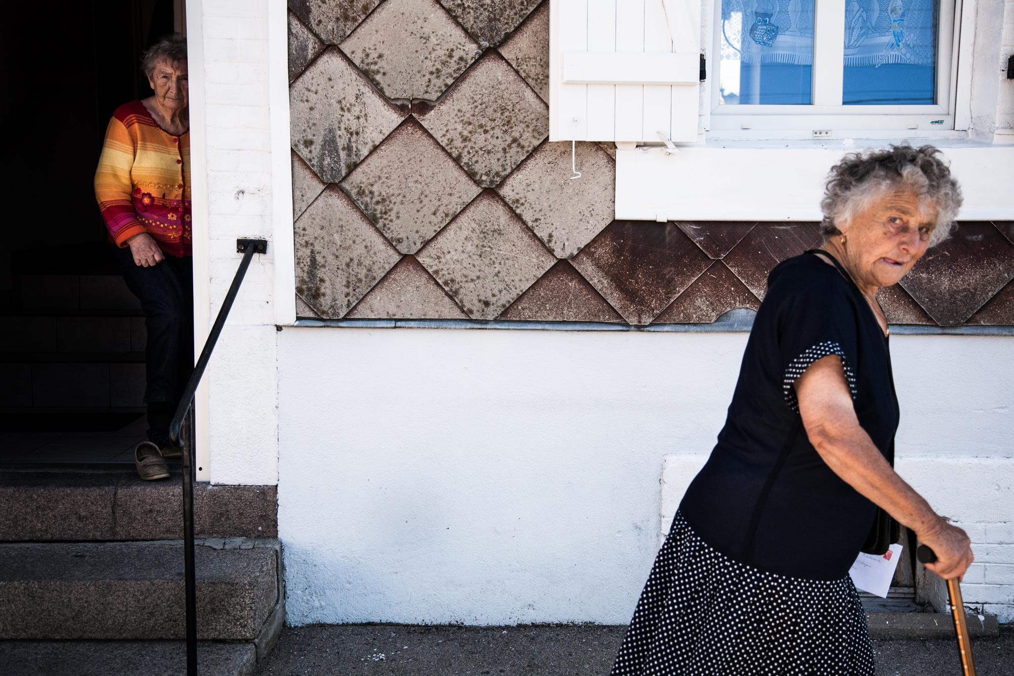 26 août 2010. Rue de la Vologne.Sous le regard d'une voisine, Georgette emporte une lettre à la boîte aux lettres. Avant, elle allait à la poste de Laveline- devant-Bruyères pour le courrier ou retirer de l'argent. « Ben, ils l'ont supprimée ». Elle a ses enfants pour l'emmener à Bruyères, à 5 km de là. « Mais les anciens qui n'ont personne, je ne sais pas... »  Extrait du projet webdocumentaire   Les Pieds dans la France  , co-réalisé avec Stéphane Doulé et Camille Millerand.
