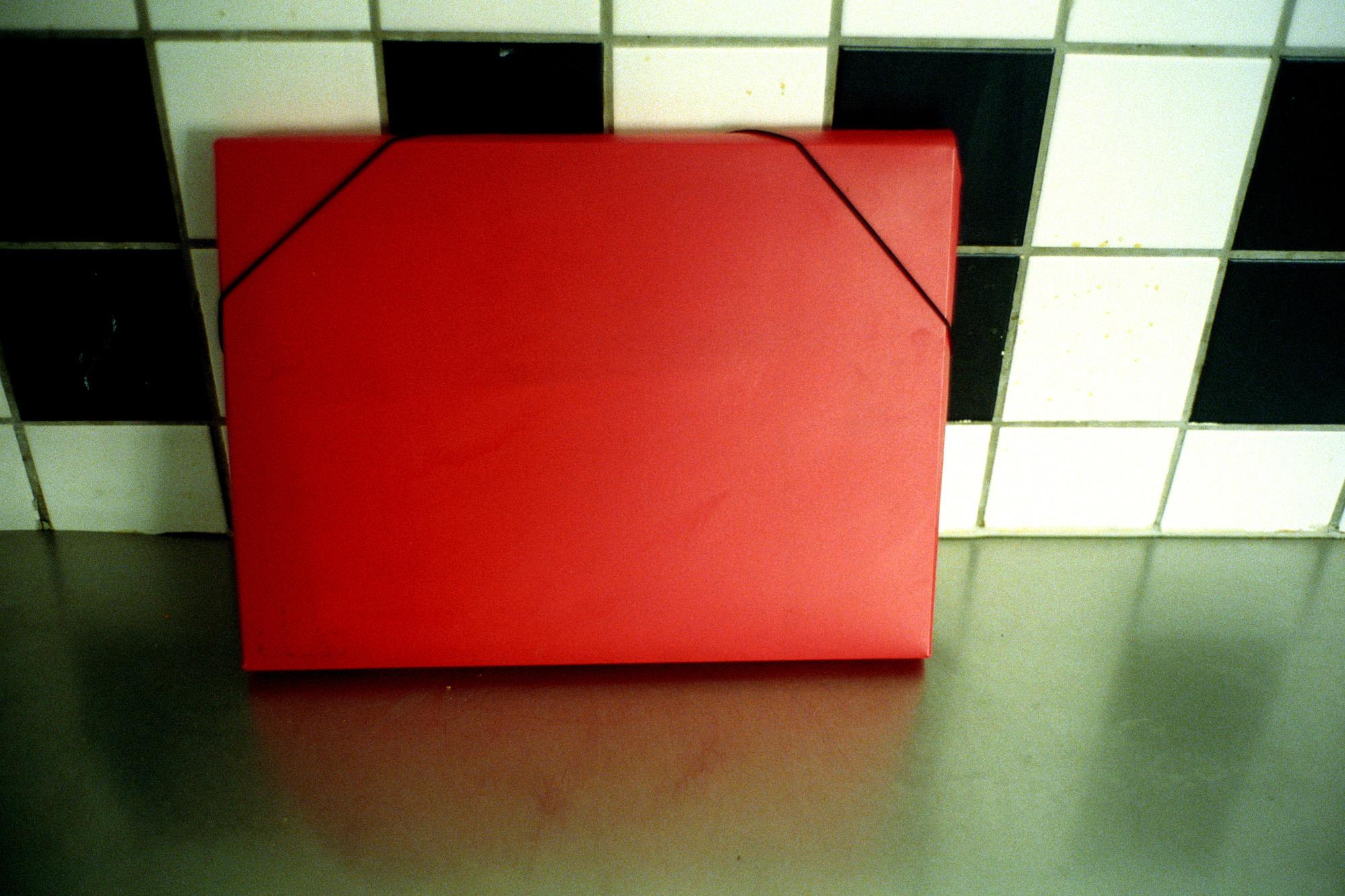 """C'est A., rencontré dans une cuisine. Il est fier de me montrer sa pochette rouge, dans laquelle est toute sa vie. Les papiers administratifs nécessaires à la survie en France.  Extrait du webdocumentaire   """" Adoma, vers la maison ? """"  , séléctionné au festival Visa Pour l'Image 2009."""