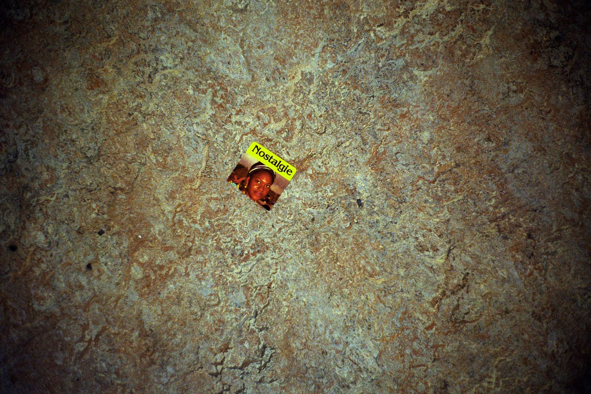 """Dans un couloir, il y a cet autocollant posé par terre.  Extrait du webdocumentaire   """" Adoma, vers la maison ? """"  , séléctionné au festival Visa Pour l'Image 2009."""